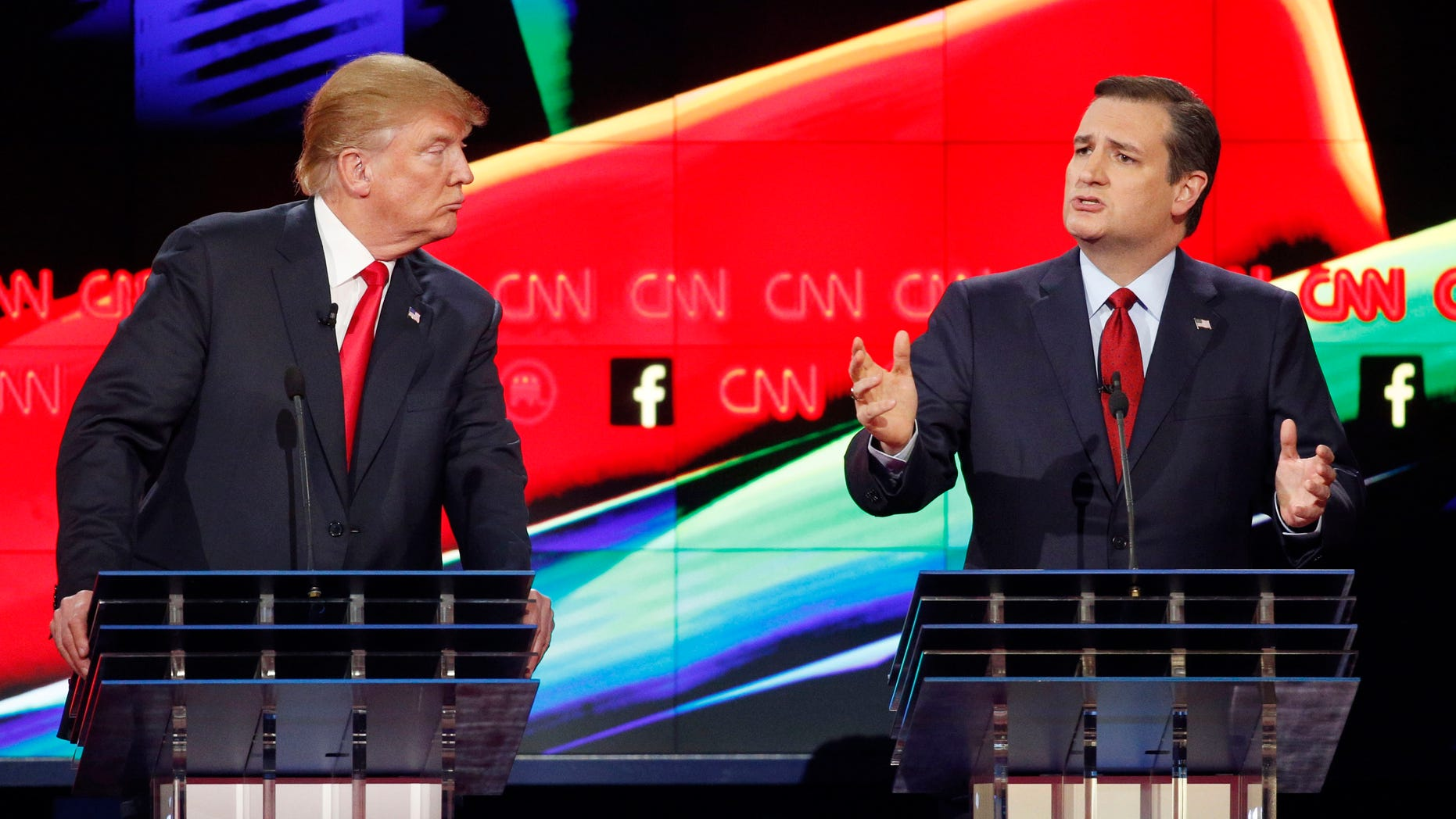 In this Dec. 15, 2015 photo, Donald Trump, left, watches as Ted Cruz speaks during the CNN Republican presidential debate at the Venetian Hotel & Casino in Las Vegas. A growing debate over Americaâs role in promoting regime change in the Middle East is creating unusual alliances among 2016 presidential candidates that cross party lines.  (AP Photo/John Locher)