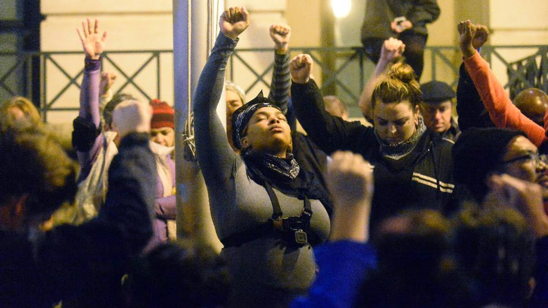 Protesters hold a moment of silence for Keith Lamont Scott in front of Charlotte-Mecklenburg Police Department headquarters, in the aftermath of no indictment being given in the death of Keith Lamont Scott, in Charlotte, N.C., Wednesday, Nov. 30, 2016. A prosecutor has cleared a Charlotte police officer in the killing of a black man whose death touched off civil unrest, and he presented detailed evidence to rebut assertions that the slain man was unarmed. Charlotte-Mecklenburg District Attorney Andrew Murray said Wednesday that Officer Brentley Vinson was justified in opening fire on Scott and won't face charges. (David T. Foster III/The Charlotte Observer via AP)