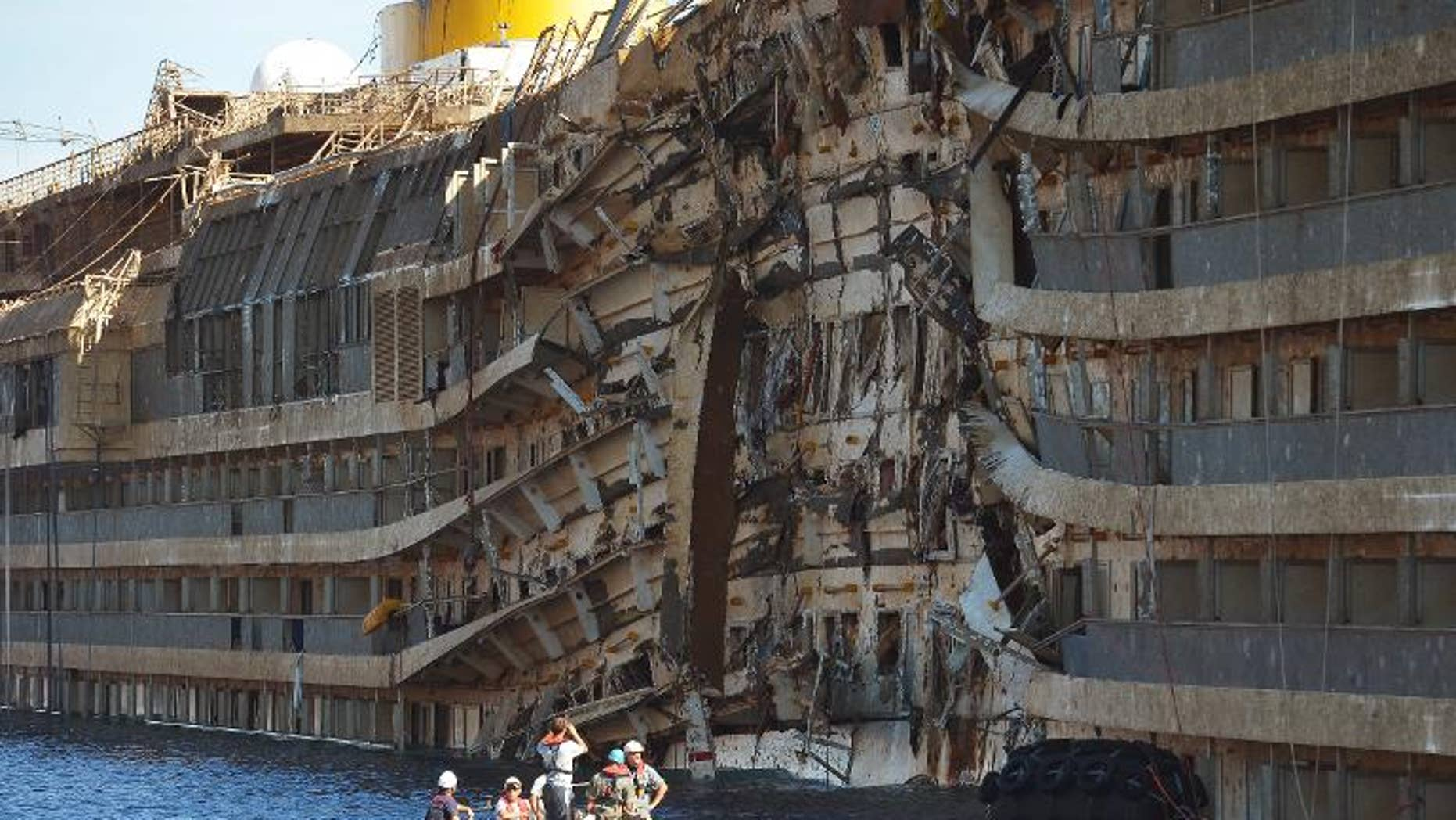 Workers from US salvage company Titan and Italian firm Micoperi inspect the wreck of the Costa Concordia cruise ship after it was hauled out of the water, in Giglio harbour on September 18, 2013