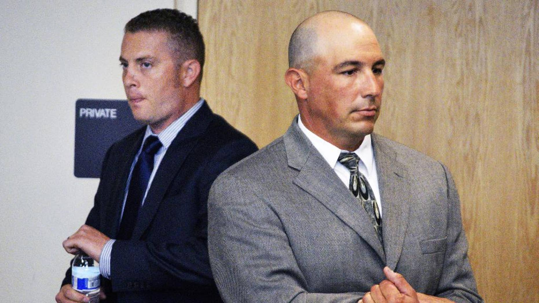 Former Albuquerque Detective Keith Sandy, center, listens to a special prosecutor tell a judge at a preliminary hearing that he unlawfully shot a homeless camper who posed no threat in Albuquerque, N.M. on Monday, Aug. 3, 2015. Sandy and Albuquerque officer Dominique Perez are facing second-degree murder charges in the 2014 fatal shooting death of 38-year-old James Boyd. (AP Photo/Russell Contreras)