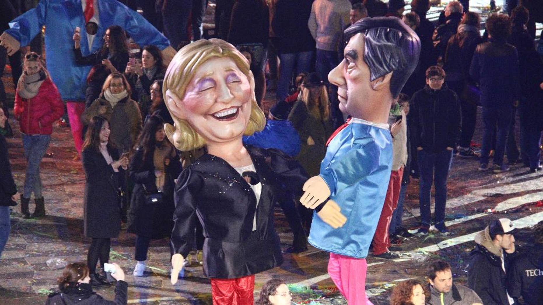 Big heads of French presidential candidates, Marine Le Pen, left, of the far-right National Front, and Francois Fillon of the right-wing Republicans party, join the Nice Carnival parade, Saturday, Feb. 11, 2017, in Nice, southeastern France. Floats in the Carnival's 133rd edition that kicked off on Saturday were led by the King of Energy, this year's theme, and followed notably by a huge Donald Trump with hair dryers trained on his crown of blond hair. (AP Photo/Henri Grivot)