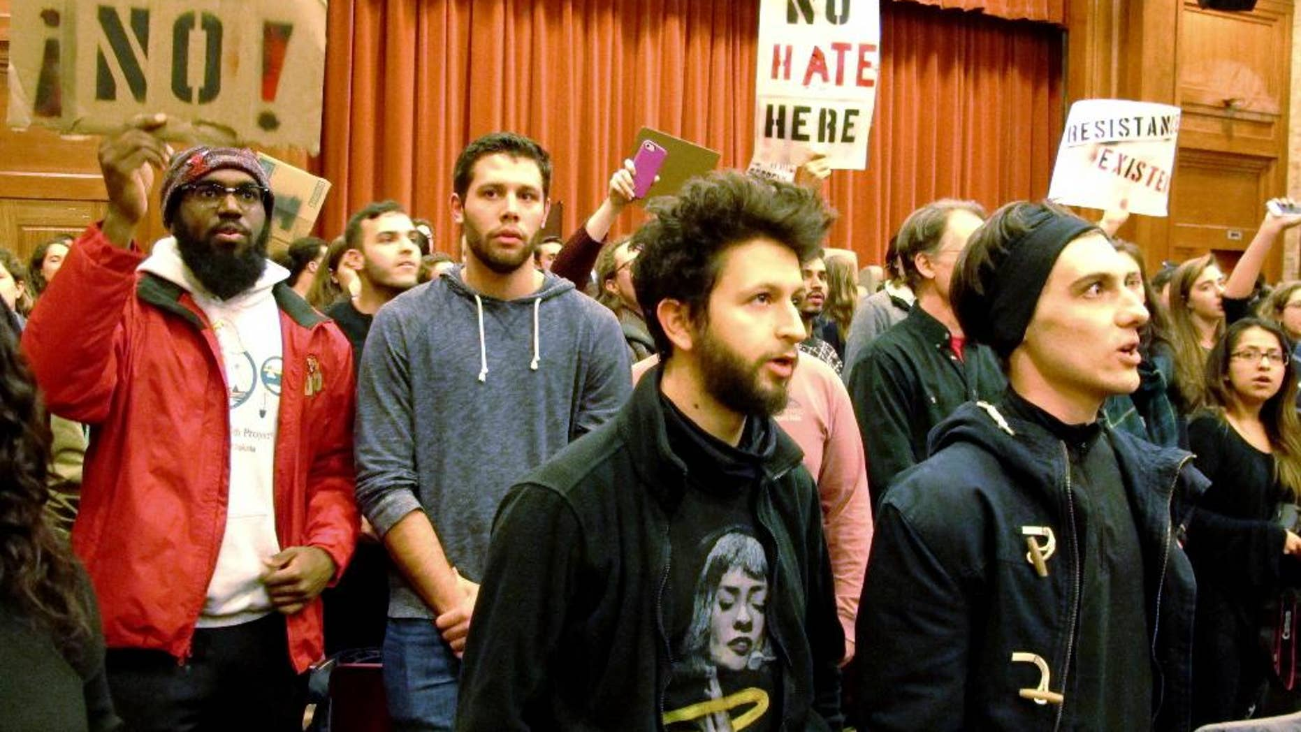 File-This March 2, 2017, file photo shows Middlebury College students turning their backs to Charles Murray, unseen, during his lecture in Middlebury, Vt. Up to 70 students face disciplinary measures over the protest of author Charles Murray, who spoke at Middlebury College in March. A professor was injured in a melee afterward.  (AP Photo/Lisa Rathke, File)