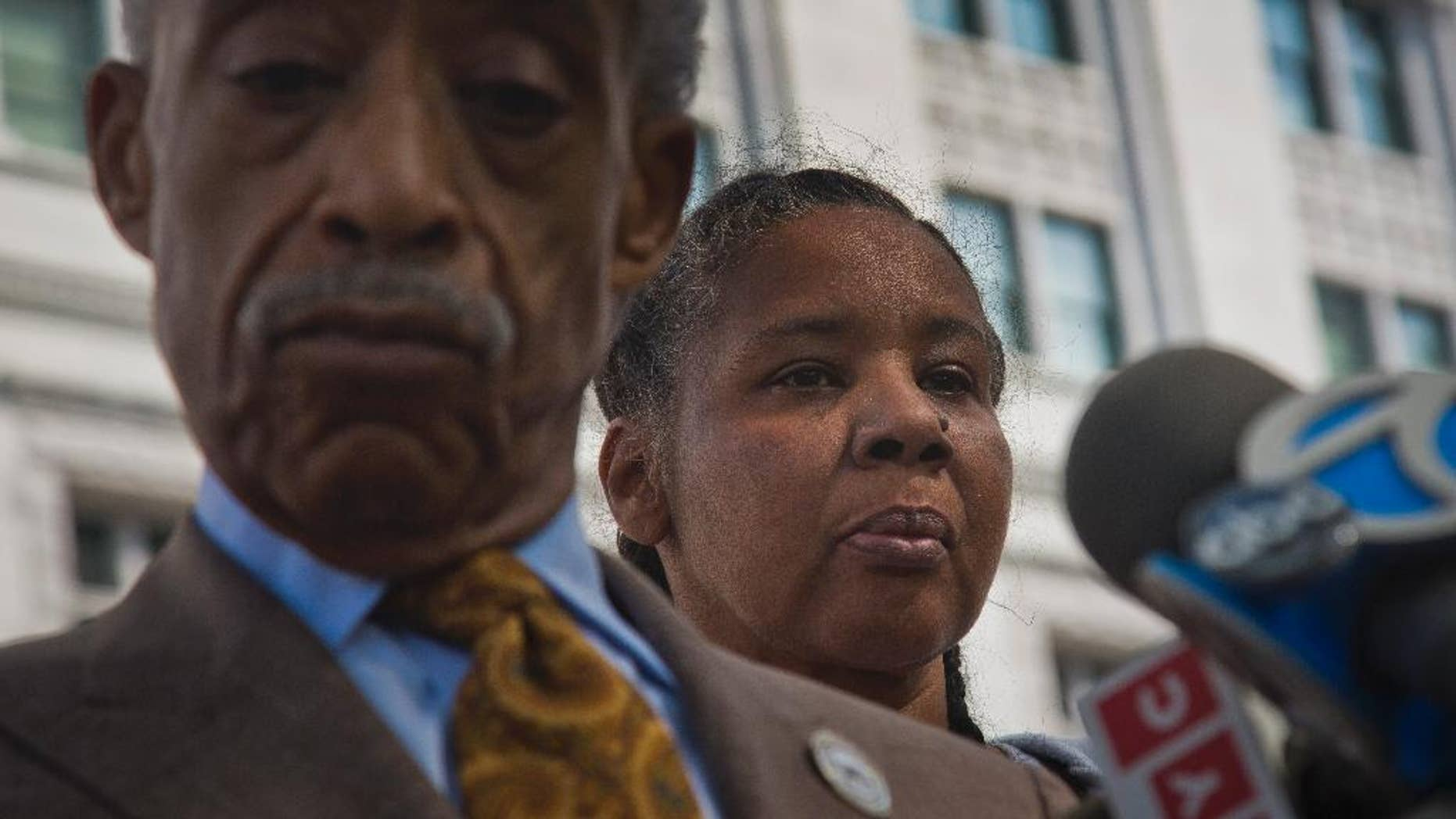 Rev. Al Sharpton, left, and Esaw Garner, the wife of fatal police chokehold victim Eric Garner, listen during a press briefing after  meeting privately with U.S. Attorney Loretta Lynch on Thursday Aug. 21, 2014 in New York.  The family of the unarmed Eric Garner, whose death last month in police custody was recorded on video, has asked federal prosecutors to investigate the case.(AP Photo/Bebeto Matthews)