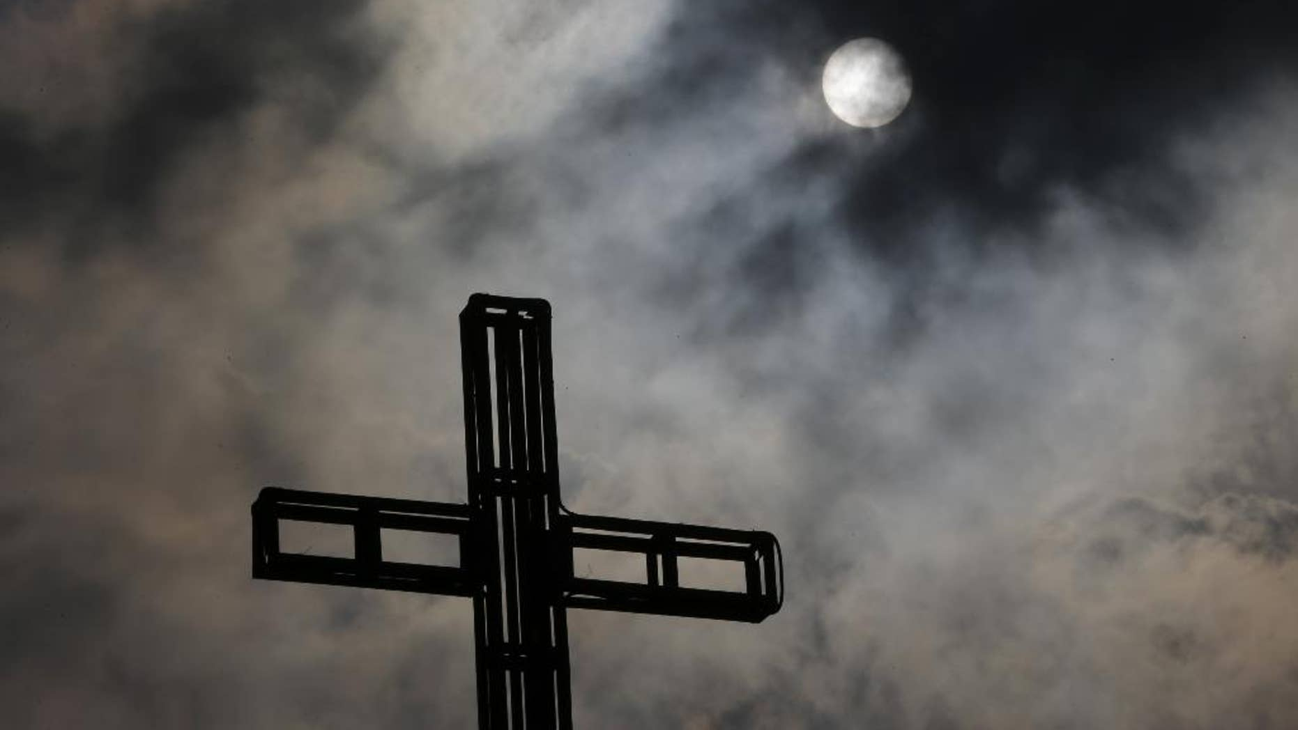Dark clouds partially cover the sun above a church on Easter Sunday April 5, 2015 in suburban Quezon city, north of Manila, Philippines.  Tropical storm Maysak weakened before hitting the Philippines' northeastern coast Sunday, driving away thousands of Lenten holiday vacationers and tourists. (AP Photo/Aaron Favila)
