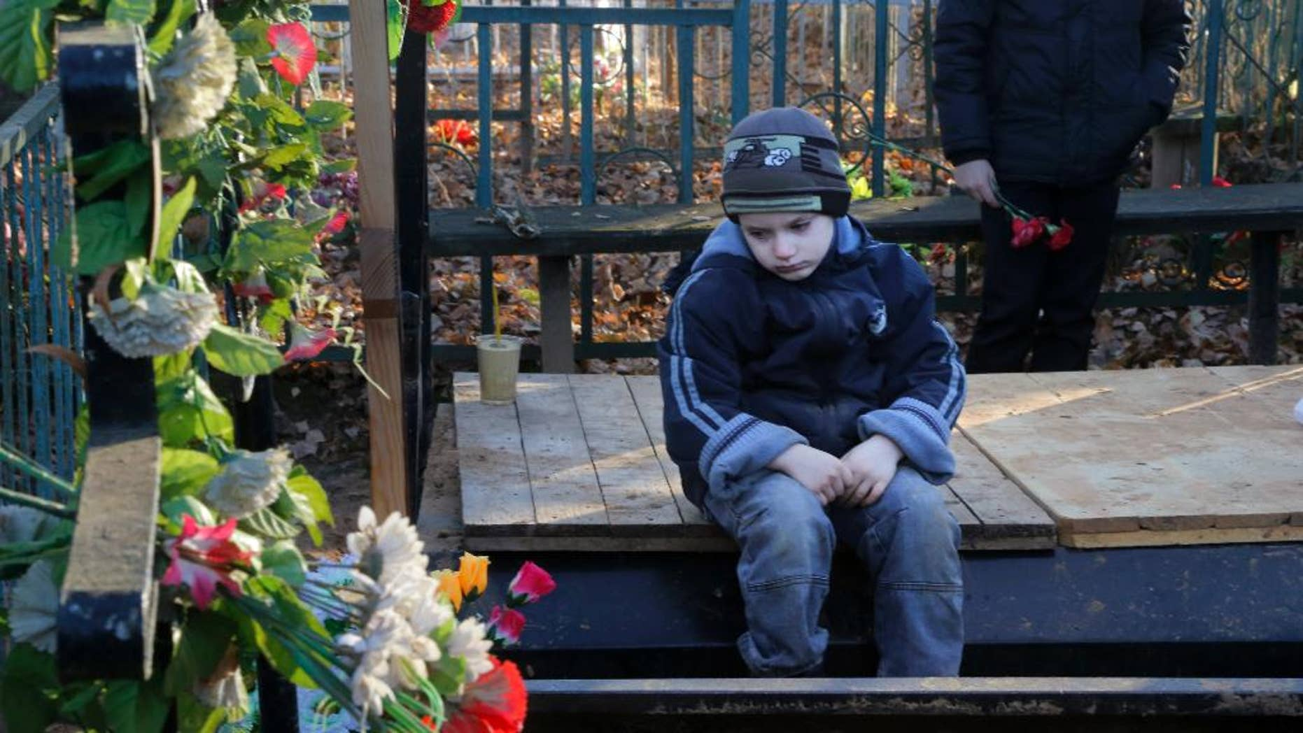Mikhail, the grandson of one of the plane crash victims  Nina Lushchenko, sits at her grave, during her funeral at a cemetery in the village of Sitnya, 80 km (about 50 miles) of Veliky Novgorod, Russia, Thursday, Nov. 5, 2015.  The first victim of Saturday's plane crash in Egypt was laid to rest on Thursday following a funeral service in a medieval church in the north Russian city of Veliky Novgorod.  Russia's Airbus 321-200 broke up over the Sinai Peninsula en route from the resort town of Sharm el-Sheikh to St. Petersburg, killing all 224 on board. (AP Photo/Dmitry Lovetsky)