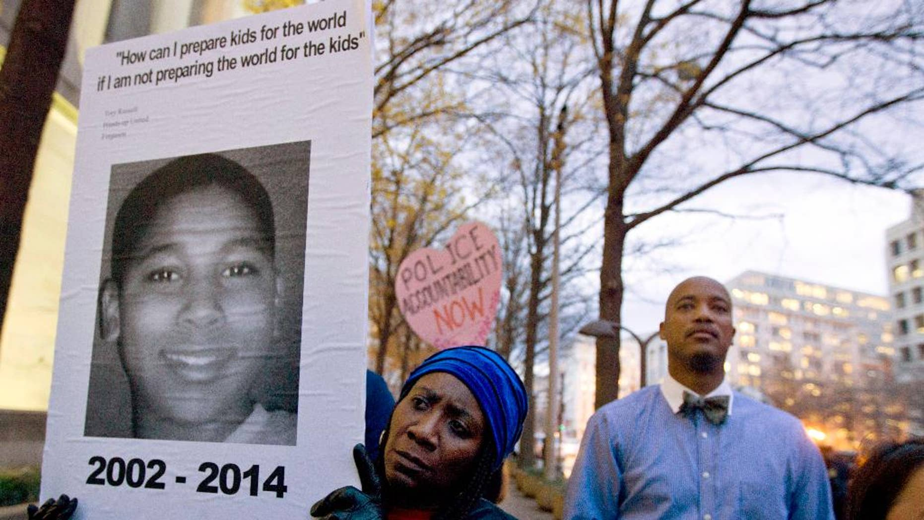 FILE - In this Dec. 1, 2014 file photo, Tomiko Shine holds up a picture of Tamir Rice during a protest in Washington. A 911 dispatcher who took a call that led to a white police officer's fatal shooting of Rice, a 12-year-old black boy who'd been playing with a pellet gun outside a Cleveland recreation center, has been suspended for eight days. Police Chief Calvin Williams stated in a disciplinary letter Constance Hollinger violated protocol. (AP Photo/Jose Luis Magana, File)