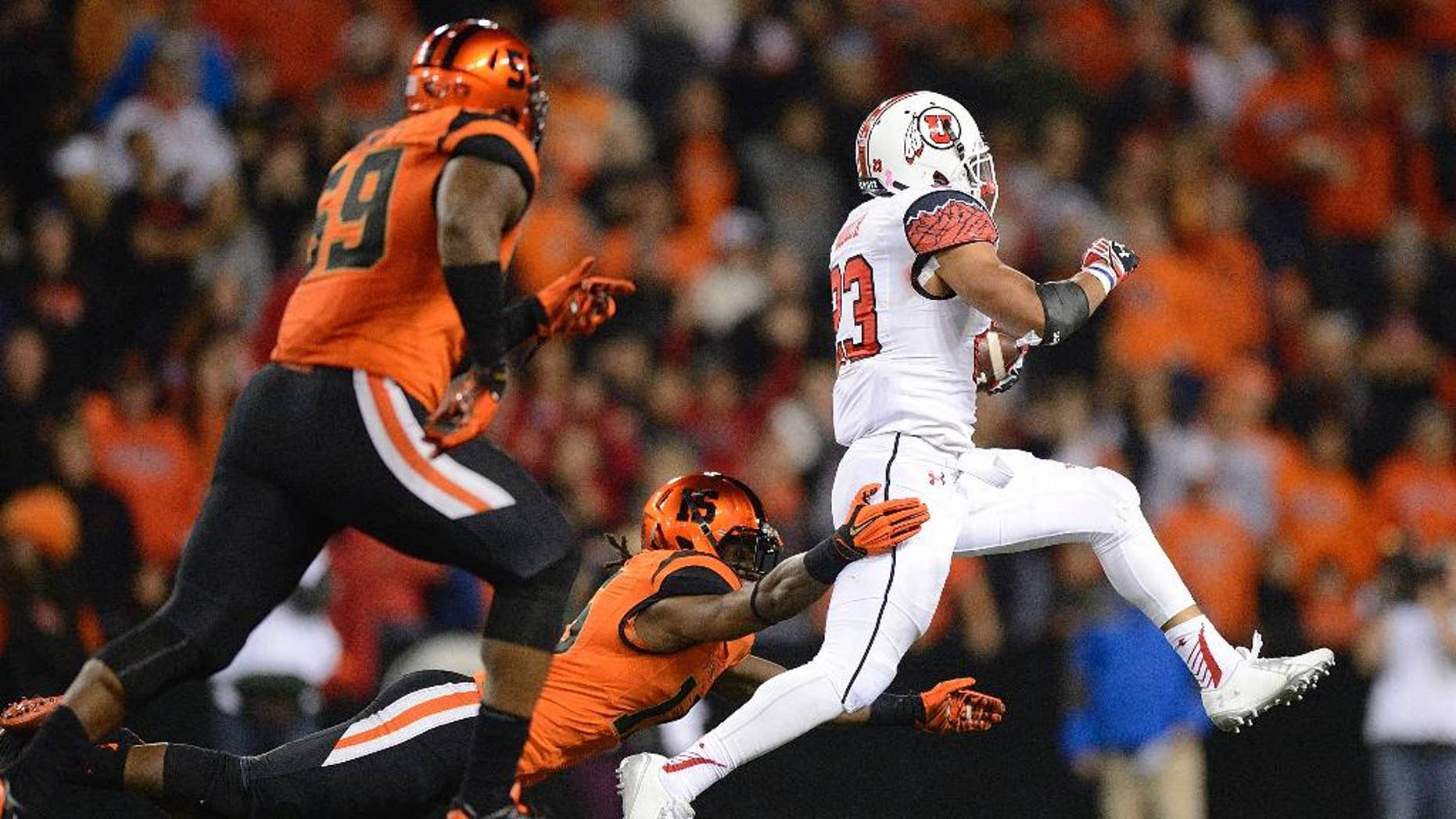 University of Utah running back Devontae Booker (23) breaks away from Oregon State defender Larry Scott (15) during an NCAA college football game in Corvallis, Ore., Thursday, Oct.. 16, 2014. The University of Utah beat Oregon State 29-23 in overtime. (AP Photo/Troy Wayrynen)