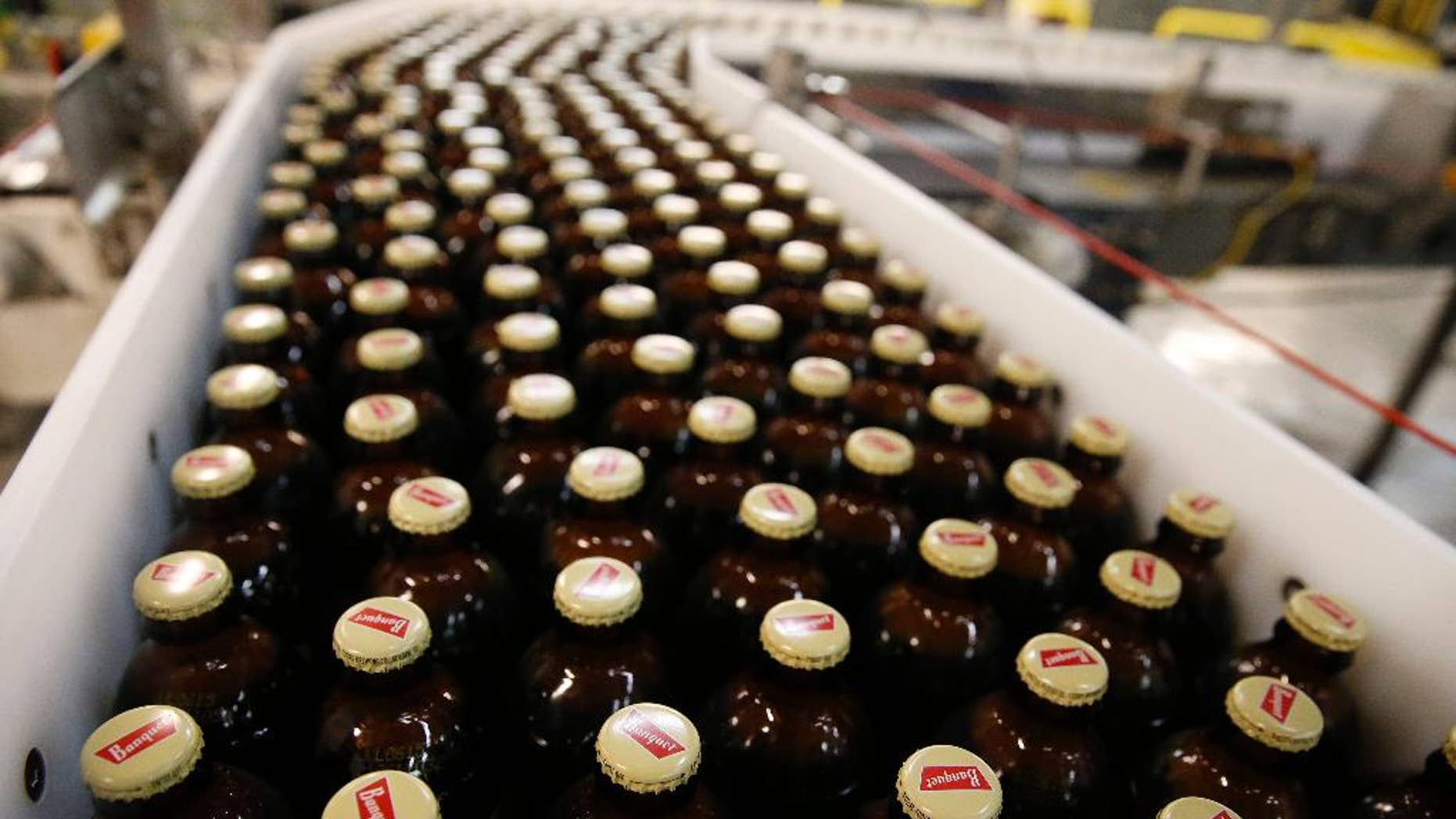 In this March 11, 2015 photo, newly-filled and sealed bottles of Coors Banquet beer move along on a conveyor belt, at the MillerCoors Brewery, in Golden, Colo. The Commerce Department releases factory orders for March on Monday, May 4, 2015. (AP Photo/Brennan Linsley)