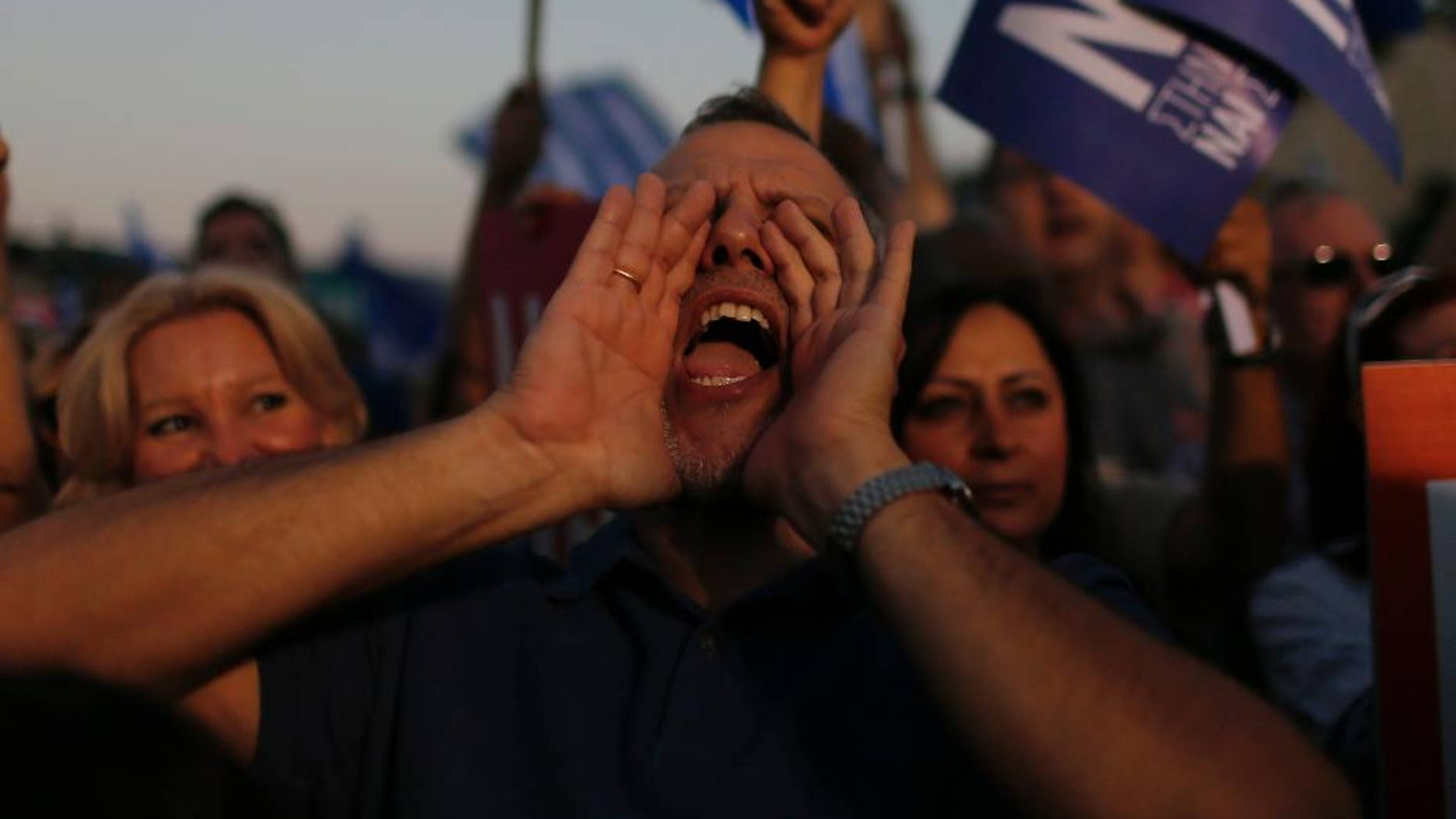 A demonstrator shouts slogans during a rally organized by supporters of the Yes vote in Athens, Friday, July 3, 2015. A new opinion poll shows a dead heat in Greece's referendum campaign with just two days to go before Sunday's vote on whether Greeks should accept more austerity in return for bailout loans. (AP Photo/Emilio Morenatti)