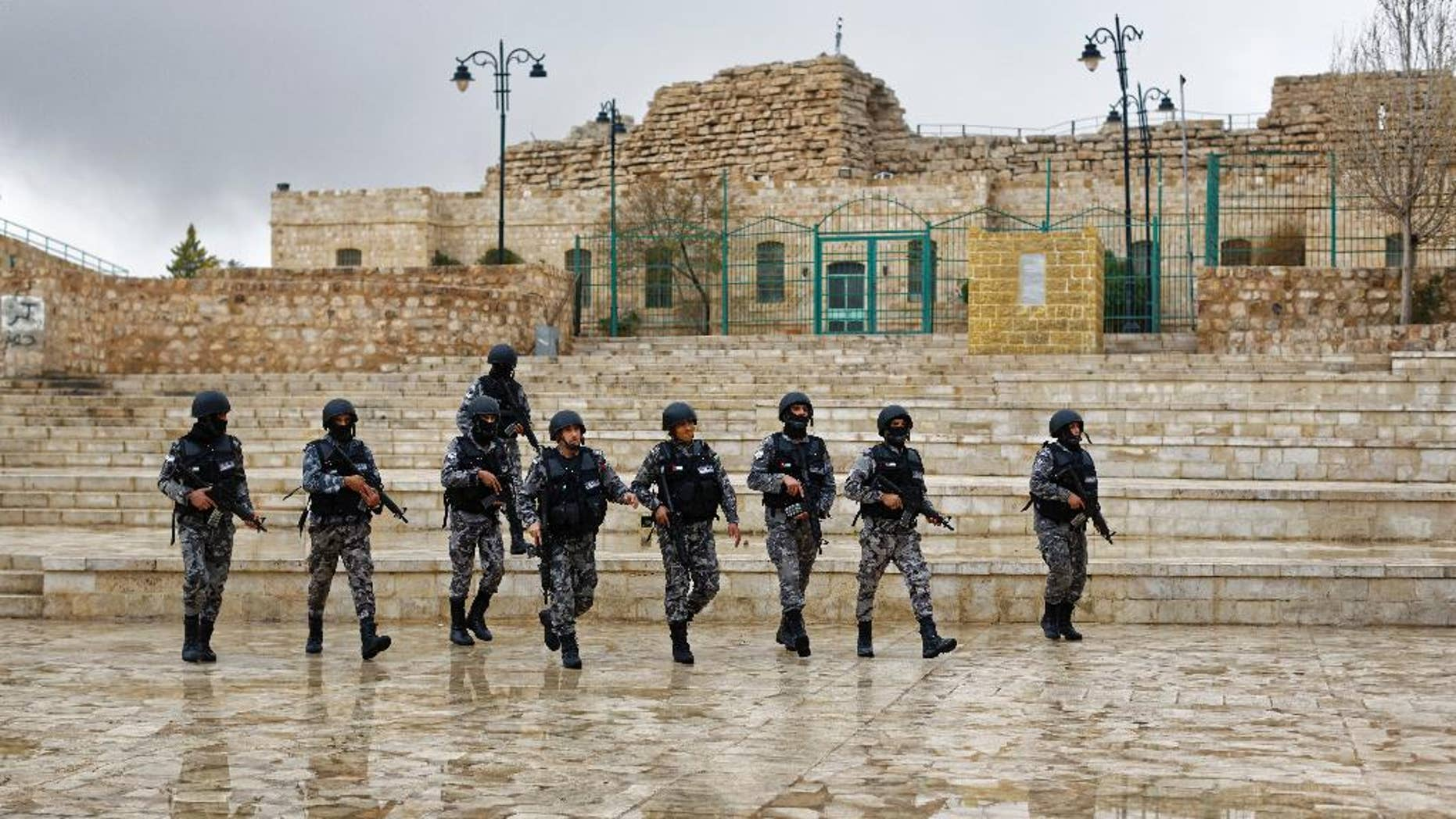 FILE -- In this Dec. 19, 2016 file photo, Jordanian security forces patrol in front of Karak Castle, where 10 people were killed on Dec. 18, 2016, in the central town of Karak, about 140 kilometers (87 miles) south of the capital Amman, Jordan. The recent Islamic State shooting rampage at Karak Castle, a popular tourism site in Jordan, could signal a more aggressive campaign by the extremist group to destabilize the pro-Western kingdom. A senior security official says members of the Karak cell, who were killed during the attack, had planned New Year's Eve attacks in Jordan, using five explosives belts. Jordan's government tries to allay concerns, saying its security forces can contain any threat. (AP Photo/Ben Curtis, File)