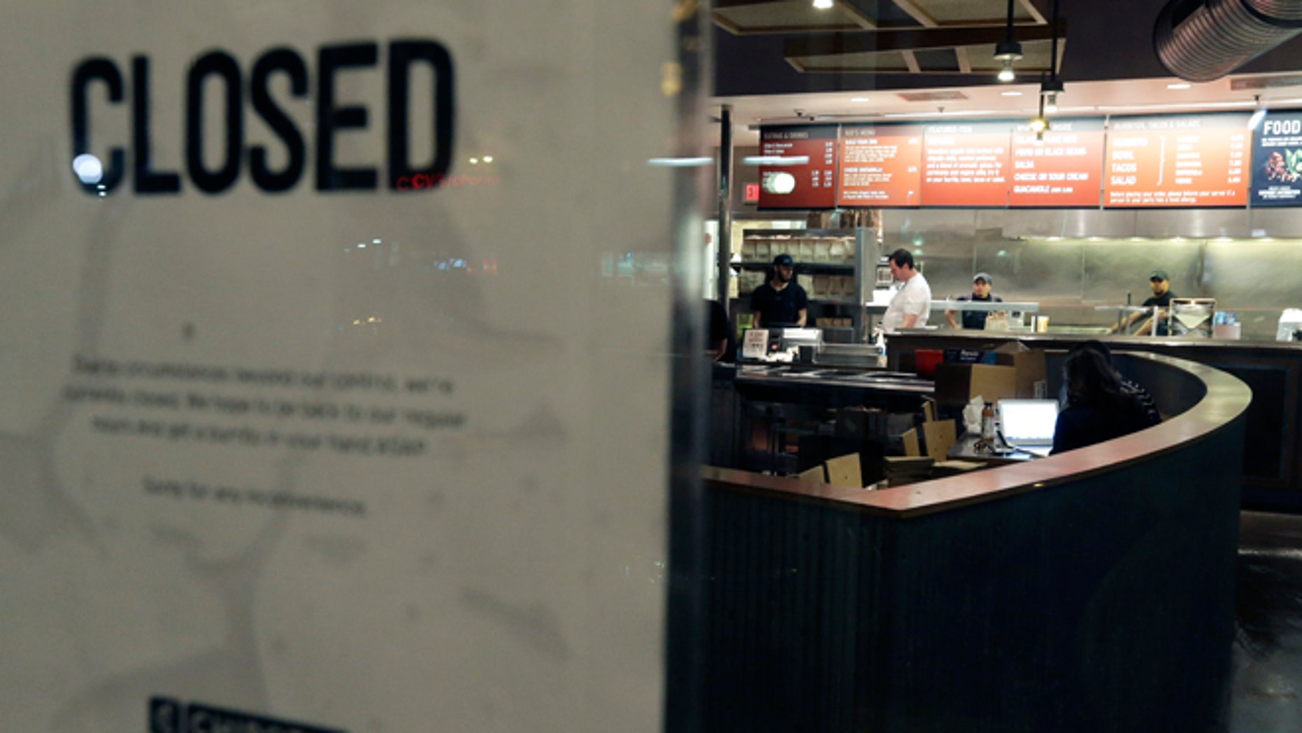 People stand inside a closed Chipotle restaurant on Monday, Dec. 7, 2015, in the Cleveland Circle neighborhood of Boston. Chipotle said late Monday that it closed the restaurant after several students at Boston College, including members of the mens basketball team, reported gastrointestinal symptoms after eating at the chain. The school said it was working with local health officials to determine the cause of the illness. (AP Photo/Steven Senne)