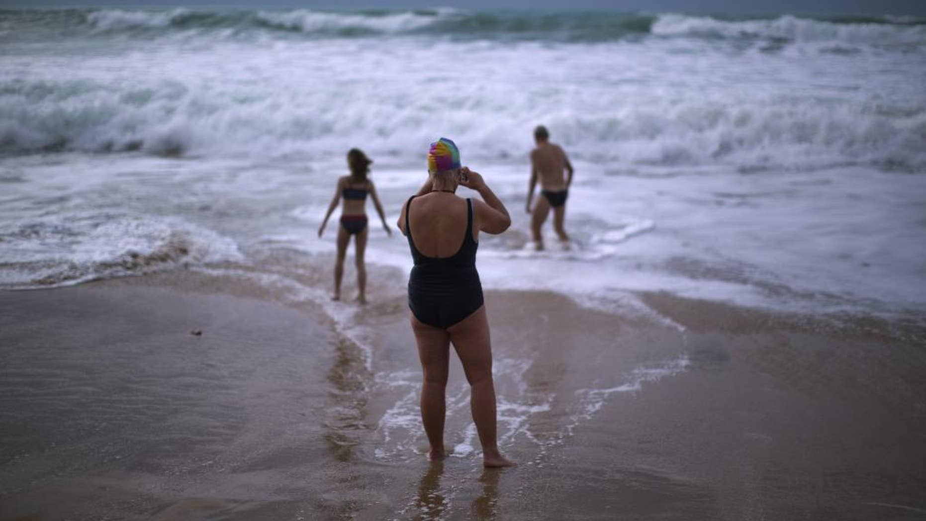 FILE- In this Jan. 1, 2014 file photo, German tourists walk on the seashore as one of them takes a photograph, after swimming in the Atlantic ocean in a beach in Cadiz, southwest Spain. Nudists have lost a seven-year legal battle for access to a popular tourist resort beach on Spain's southwestern tip. (AP Photo/Emilio Morenatti, File)
