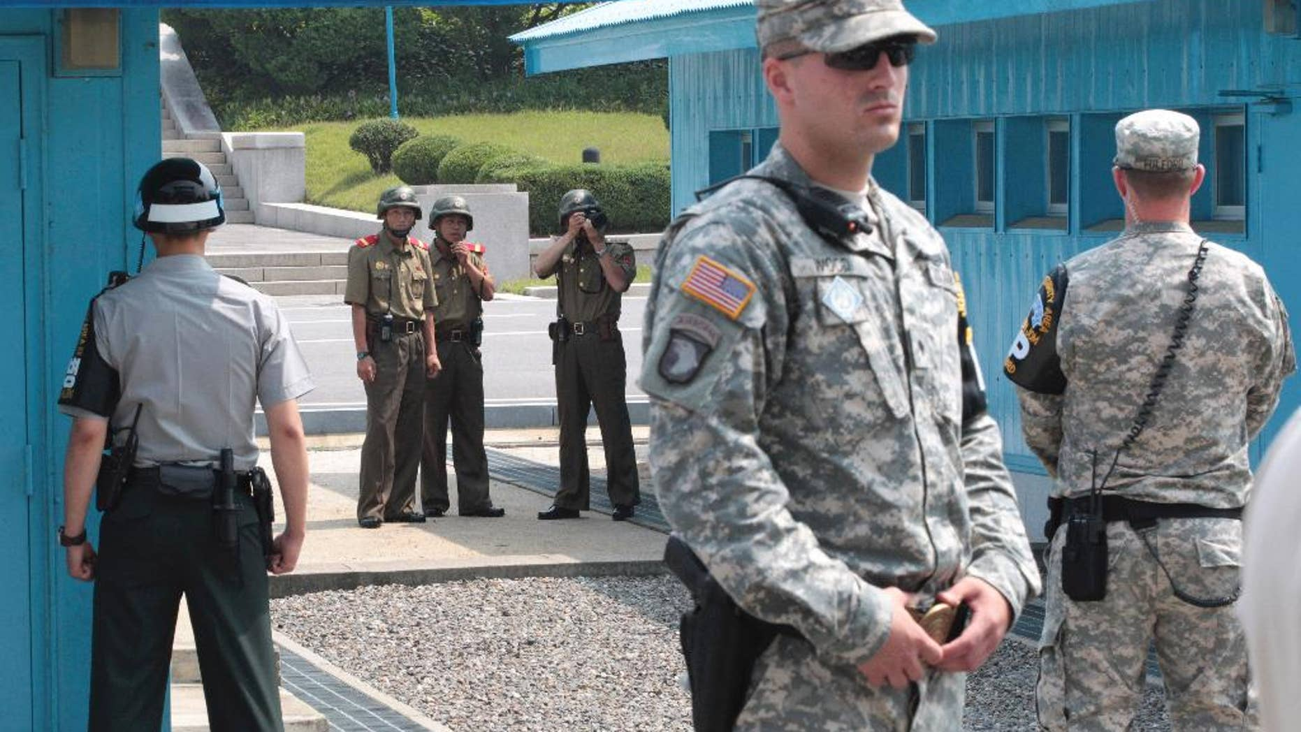 FILE - In this July 27, 2014 file photo, North Korean army soldiers watch the south side while a South Korean and United States Army soldiers stand guard at the border villages of Panmunjom in Paju, South Korea. North Korea has threatened on Saturday, Aug. 27, 2016, to aim fire at the lighting equipment used by American and South Korean troops at a truce village inside the Demilitarized Zone that divides the two Korea. (AP Photo/Ahn Young-joon, File)