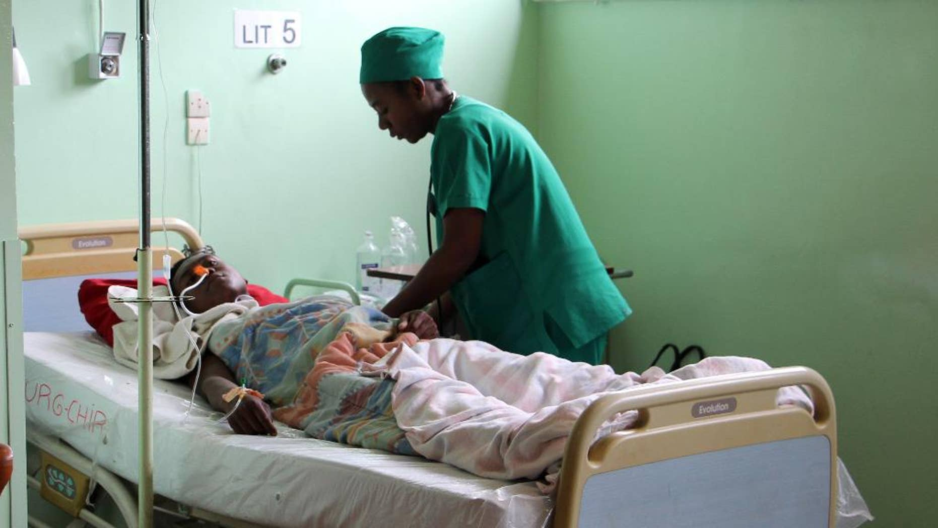 A person is treated, at a public hospital in Antananarivo, Madagascar, Monday, June 27, 2016, a day after an explosion at a stadium.  A grenade exploded in a stadium in Madagascar, killing two people and injuring more than 80 in what authorities describe as a terrorist attack, authorities said Monday. (AP Photo/Jeanne Richard)