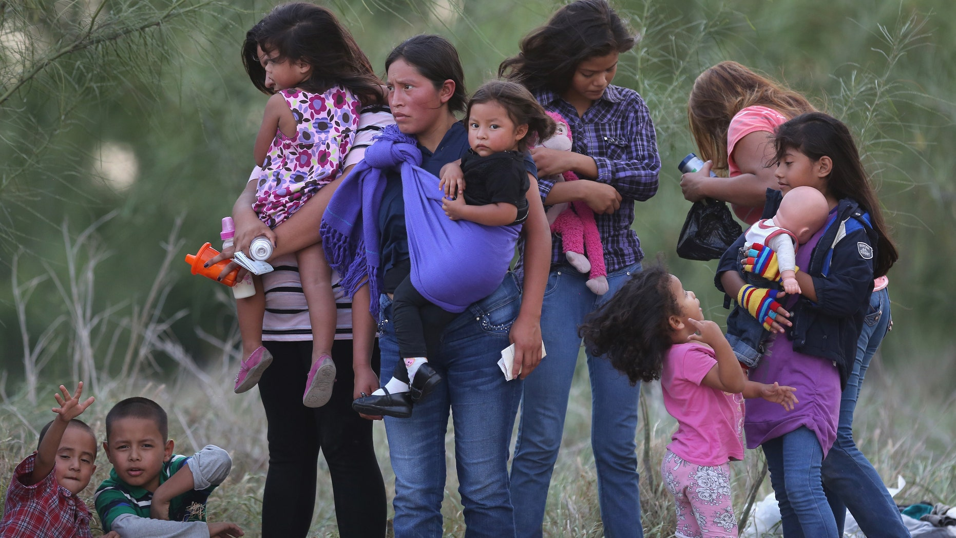 MISSION, TX - JULY 24:  Central American immigrants await transportation to a U.S. Border Patrol processing center after crossing the Rio Grande from Mexico into the Texas on July 24, 2014 near Mission, Texas. Tens of thousands of undocumented immigrants, many of them families or unaccompanied minors, have crossed illegally into the United States this year and presented themselves to federal agents, causing a humanitarian crisis on the U.S.-Mexico border. The Rio Grande Sector of the border has the heaviest traffic of illegal crossings of the entire U.S.-Mexico border.  (Photo by John Moore/Getty Images)
