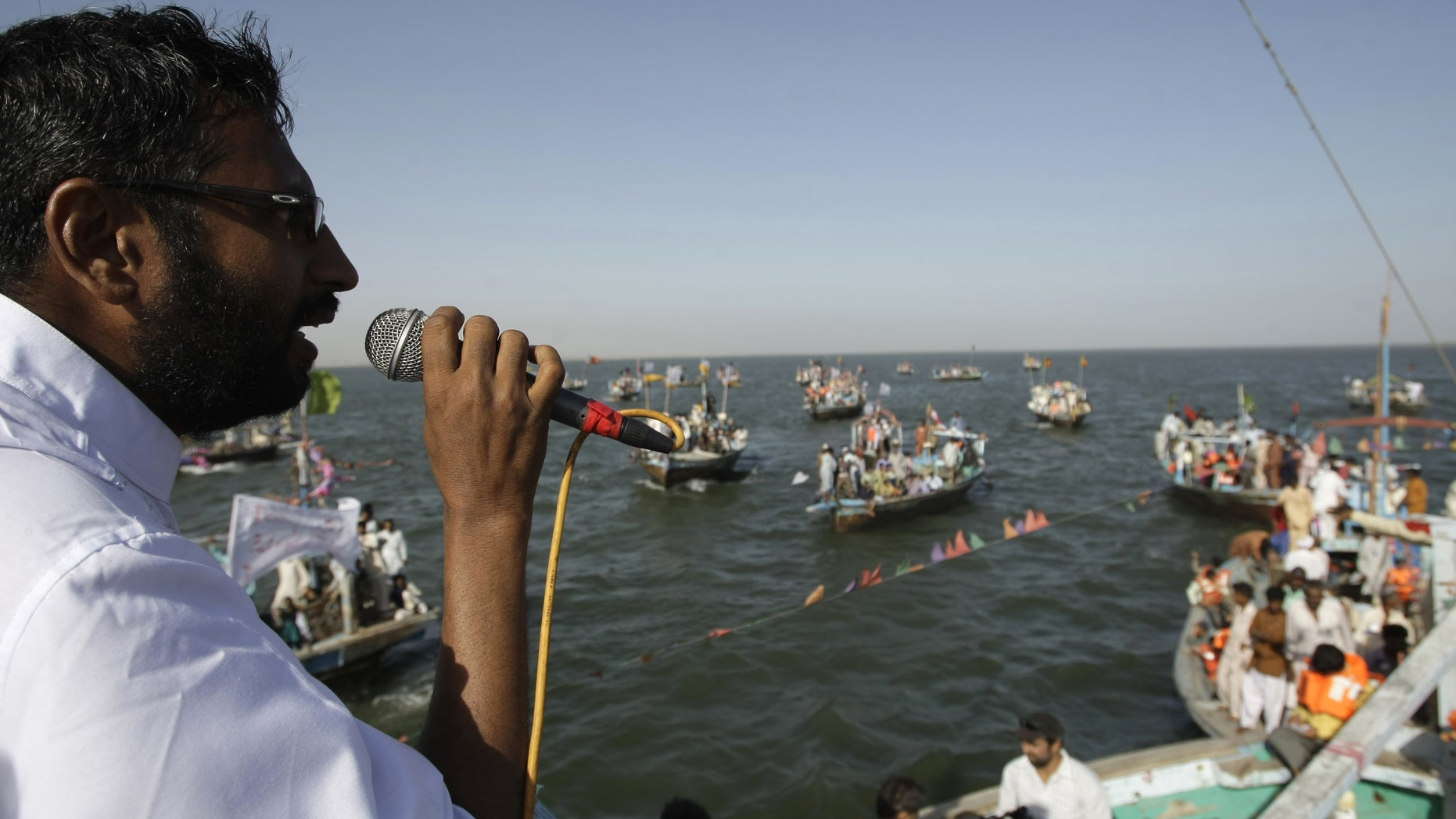 Pakistani election candidate Usman Ghani addresses fishermen living in his constituency during a campaign in the Arabian Sea near the coastal area of Karachi, Pakistan on Friday, May 3, 2013. Pakistan is scheduled to hold parliamentary elections on May 11, the first transition between democratically elected governments in a country that has experienced three military coups and constant political instability since its creation in 1947. (AP Photo/Fareed Khan)