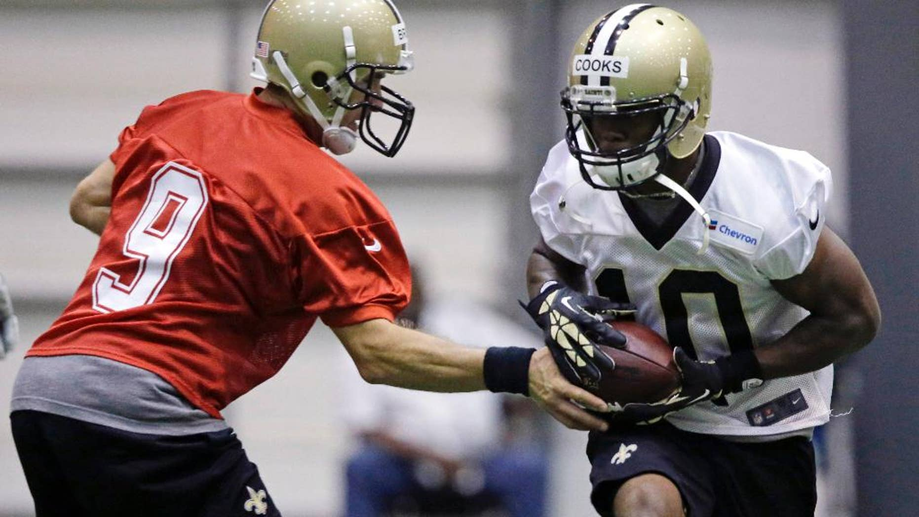 New Orleans Saints quarterback Drew Brees (9) hands off to first round draft pick Brandin Cooks (10) during NFL football minicamp  at the team's training facility in Metairie, La., Thursday, June 19, 2014. (AP Photo/Gerald Herbert)