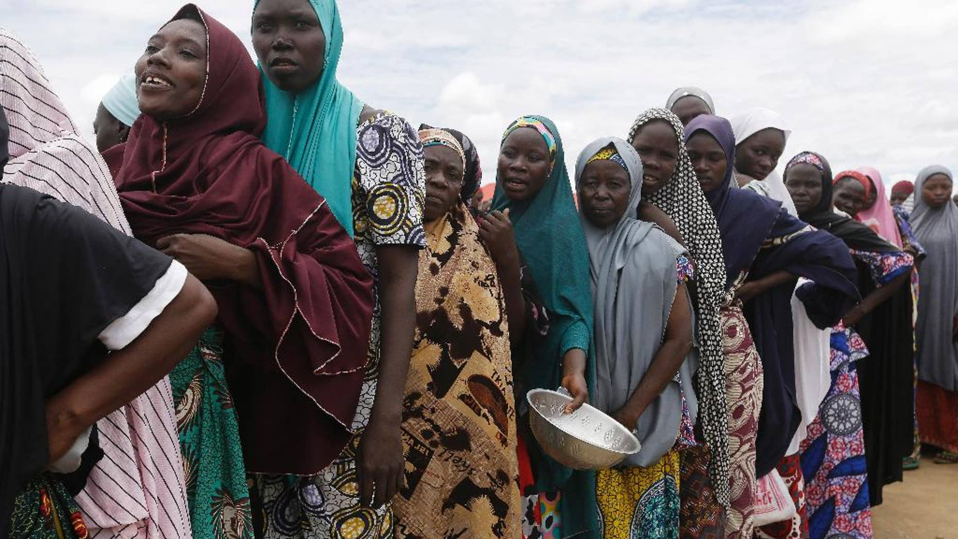 FILE-In this file photo taken Saturday, Aug. 27, 2016, women displaced by Islamist extremists wait for food to be handed out to them at the Bakassi camp in Maiduguri, Nigeria. Many say the dangerous journey is preferable to the hunger, humiliation and inhumane conditions in refugee camps where more than 1 million Nigerians, displaced by Boko Haram, are waiting to go home. Many are in Maiduguri, the biggest city in the northeast, the birthplace of Boko Haram, which has killed more than 20,000 and forced 2.6 million from their homes. (AP Photo/Sunday Alamba,File)