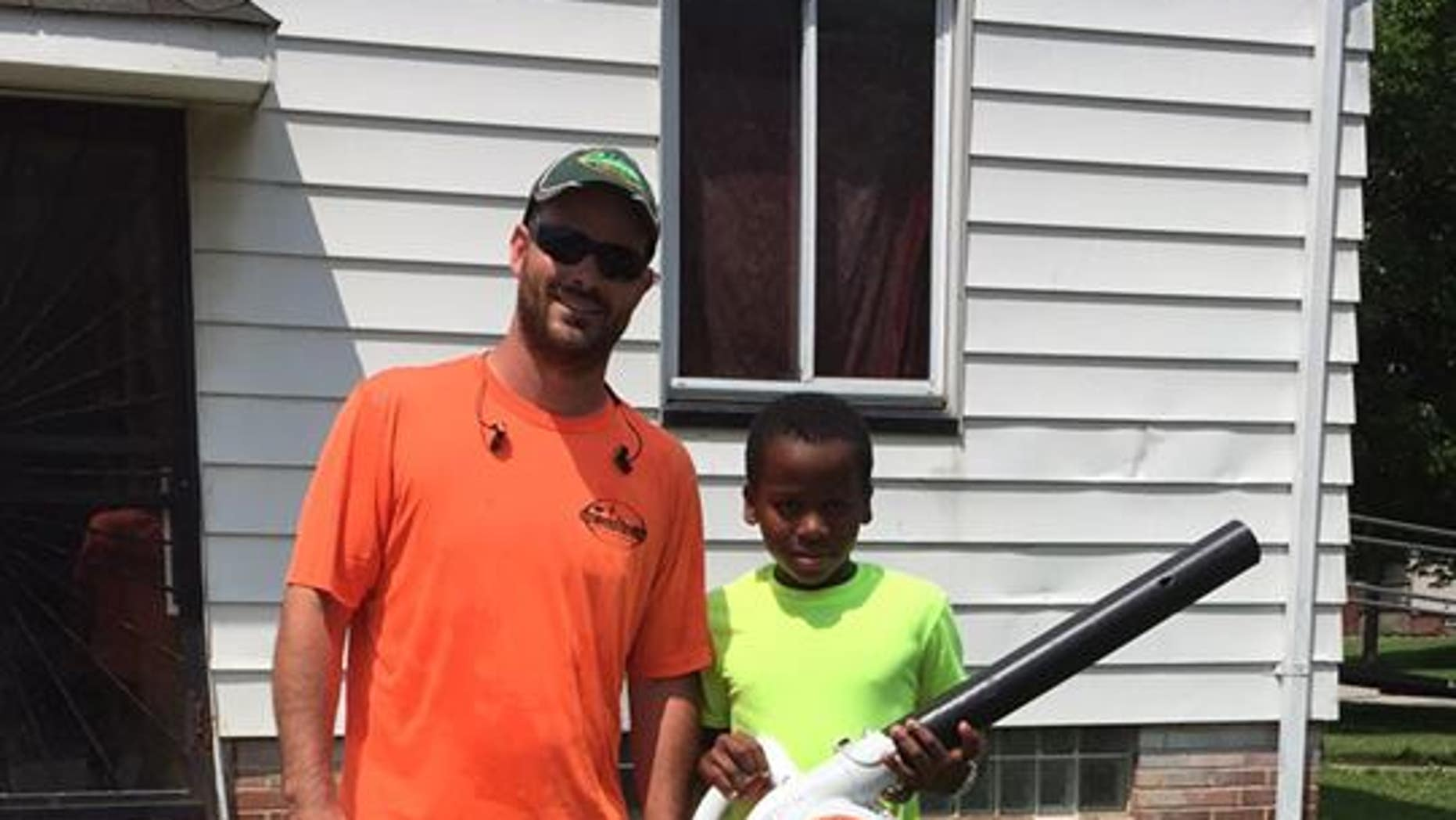 Reggie (right) poses for a photo with a man who gave him a leaf blower.