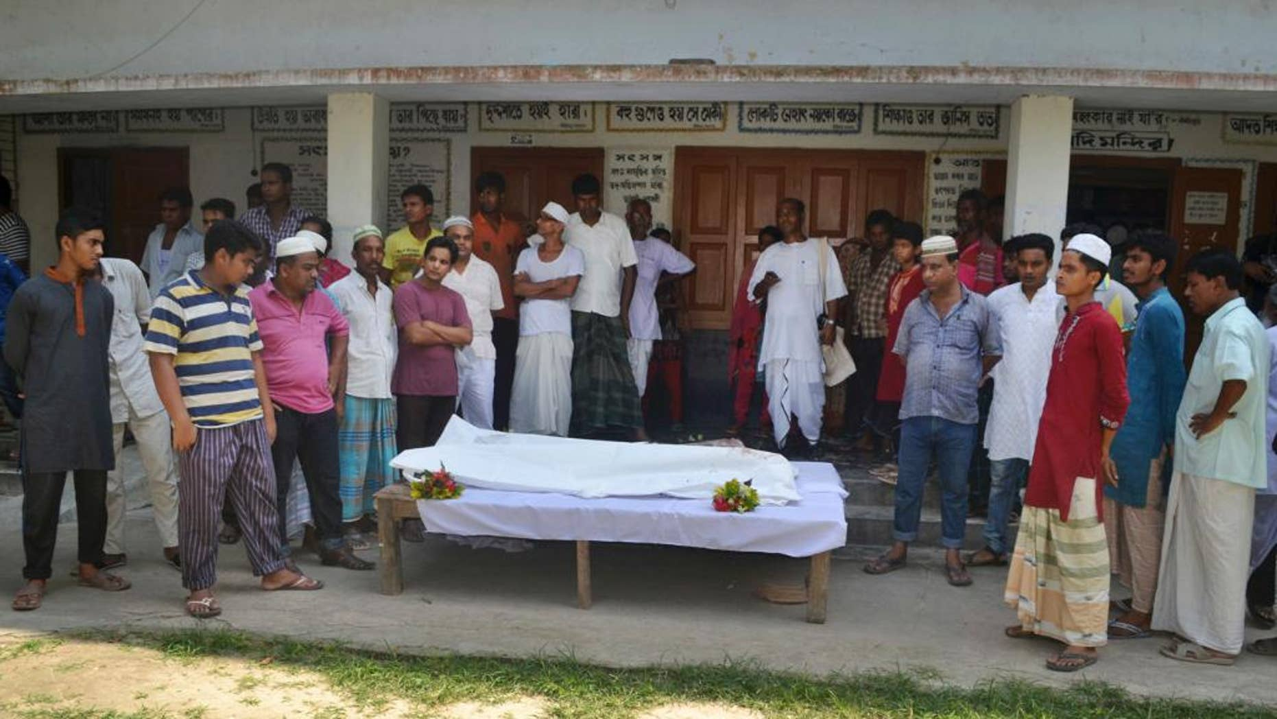 Locals surround the body of a Hindu holy man after assailants hacked him to death in Pabna, 275 kilometres (170 miles) from Dhaka, Friday, June 10, 2016. Pabna district police chief Alamgir Kabir said that radical Islamists are suspected of carrying out the attack on 60-year-old Nitya Ranjan Pandey while he was taking a walk at dawn near his ashram. (AP Photo)