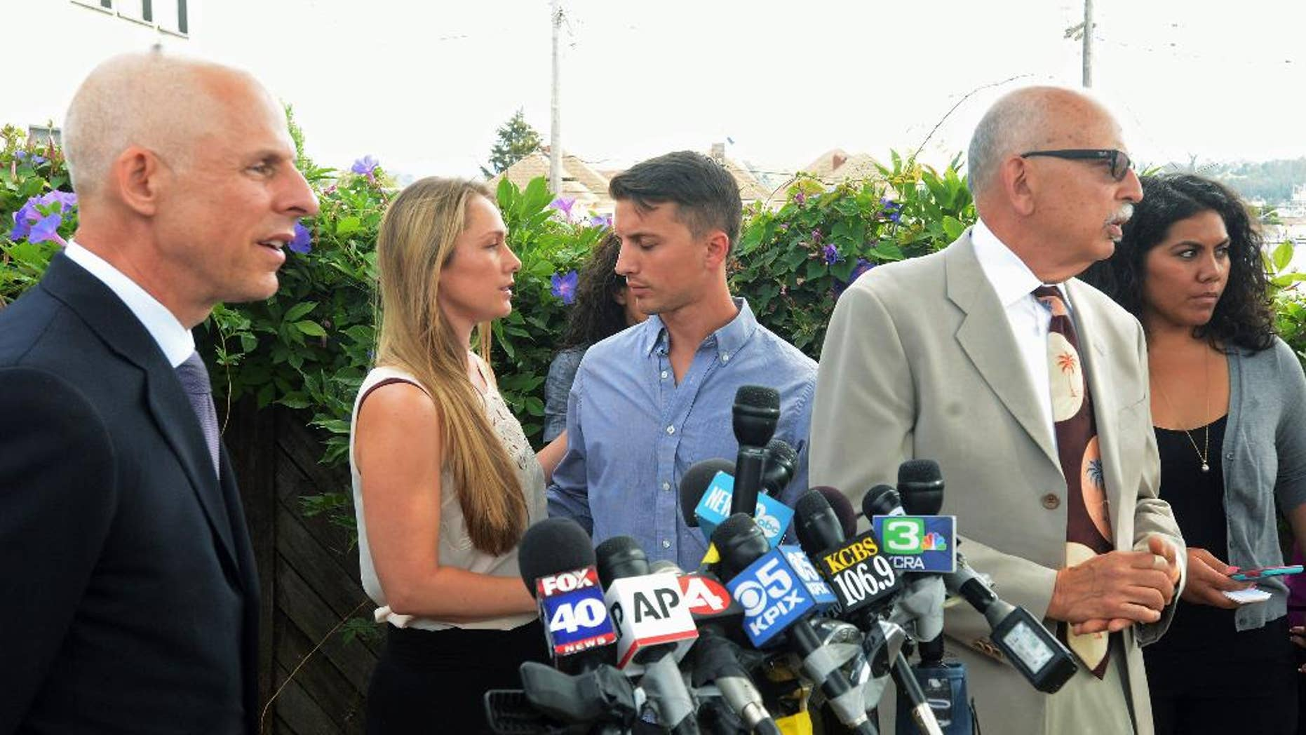 Denise Huskins, second from left, and her boyfriend, Aaron Quinn, turn to each other at the end of a news conference on Monday, July 13, 2015, in Vallejo, Calif. At left is Huskins' attorney, Douglas Rappaport and second from right is Quinn's attorney, Daniel Russo. The lawyers for the couple in the kidnap-for-ransom case that police called a hoax are blasting investigators and asking that authorities set the record straight. (Mike Jory/Vallejo Times-Herald via AP)