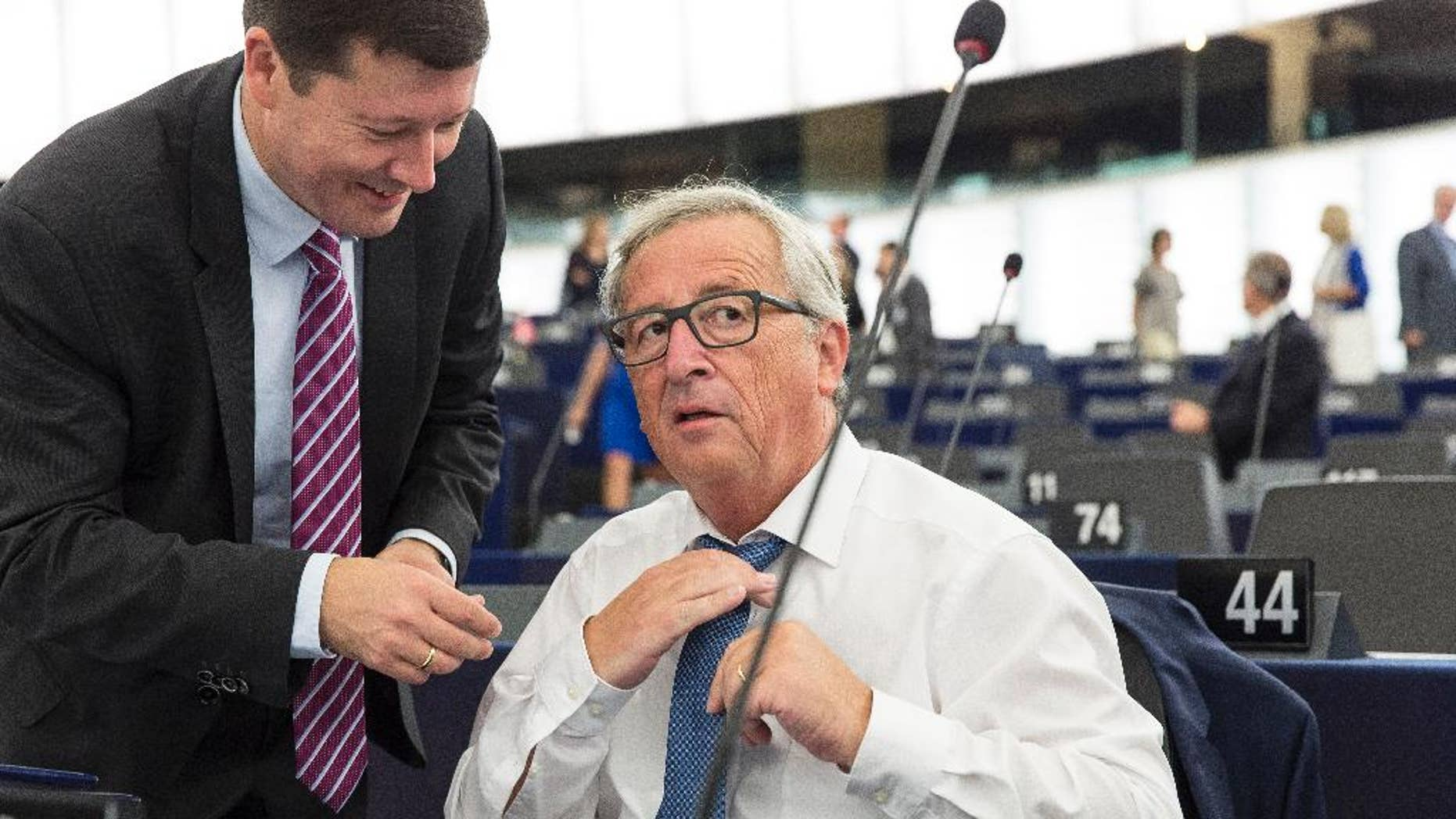 """The head of the European Union's executive, Jean-Claude Juncker, adjusts his tie next to the head of the president's cabinet, Martin Selmayer, left, as he prepares to deliver his State of the Union address at the European Parliament in Strasbourg, eastern France, Wednesday, Sept. 14, 2016. EU Commission President Jean-Claude Juncker said in his State of the European Union address to the European parliament that the EU """"still does not have enough Union.""""(AP Photo/Jean-Francois Badias)"""