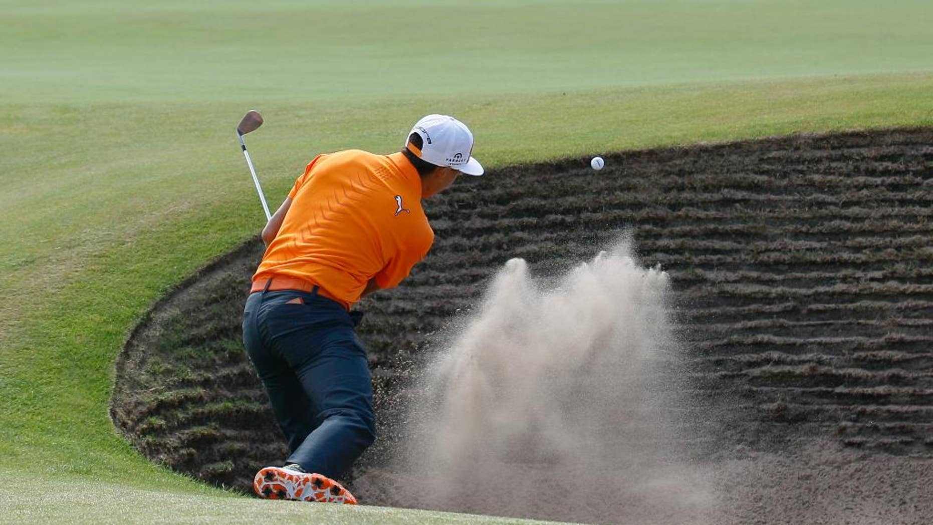 Rickie Fowler of the US plays out of a bunker on the 6th green during the final round of the British Open Golf championship at the Royal Liverpool golf club, Hoylake, England, Sunday July 20, 2014. (AP Photo/Peter Morrison)