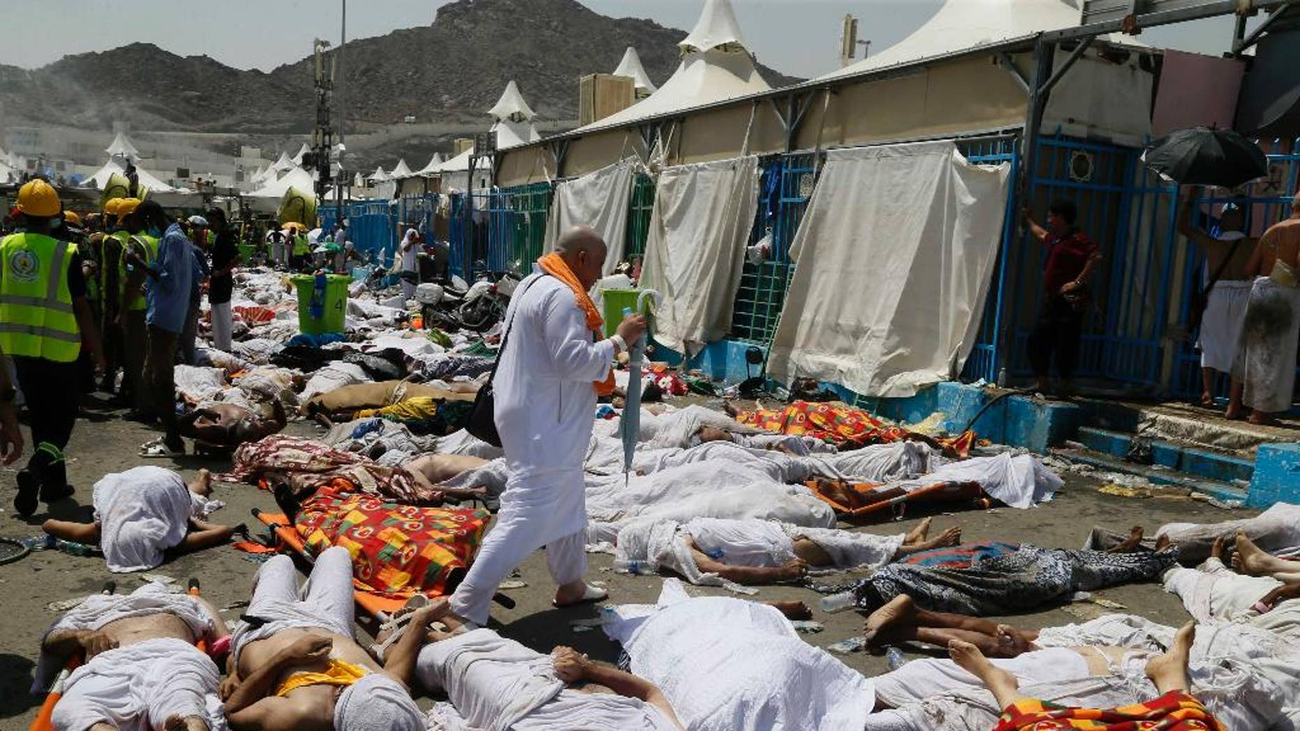 FILE - In this Thursday, Sept. 24, 2015 file photo, a Muslim pilgrim walks through the site where dead bodies are gathered in Mina, Saudi Arabia during the annual hajj pilgrimage. The crush and stampede that struck the hajj last month in Saudi Arabia killed at least 2,121 pilgrims, a new Associated Press tally showed Monday, after officials in the kingdom met to discuss the tragedy. (AP Photo, File)