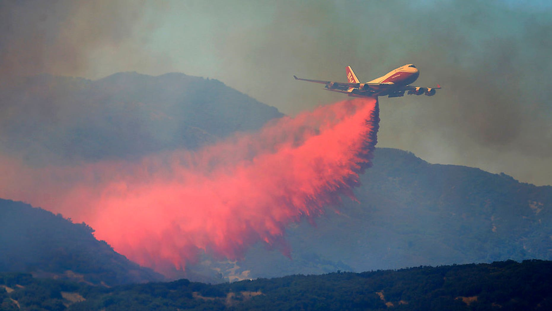 A 747 Global air tanker makes a drop on a wildfire in Scotts Valley, Friday, Aug. 3, 2018, near Lakeport, Calif. (Kent Porter /The Press Democrat via AP)