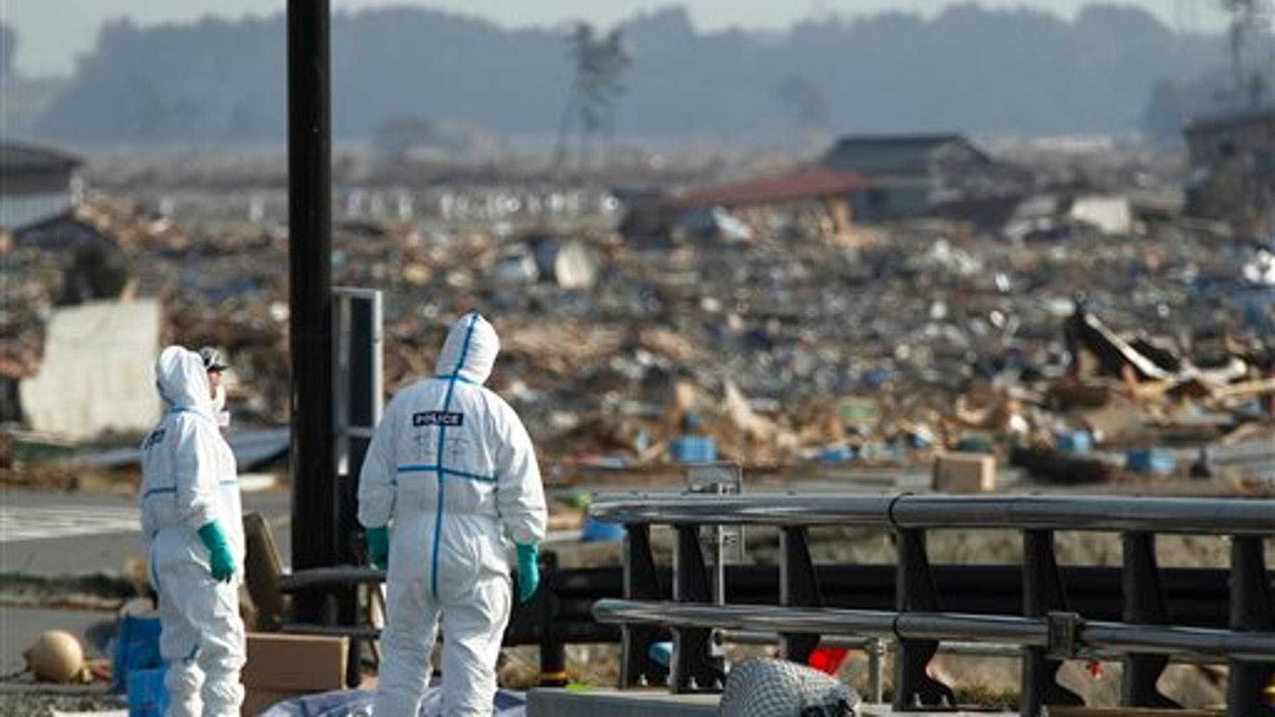 April 15: Japanese police officers stand by bodies of victims while searching for missing people at a devastated area in Namie of Fukushima Prefecture, northeastern Japan. In the background is part of the Fukushima Dai-ichi nuclear complex. (AP)