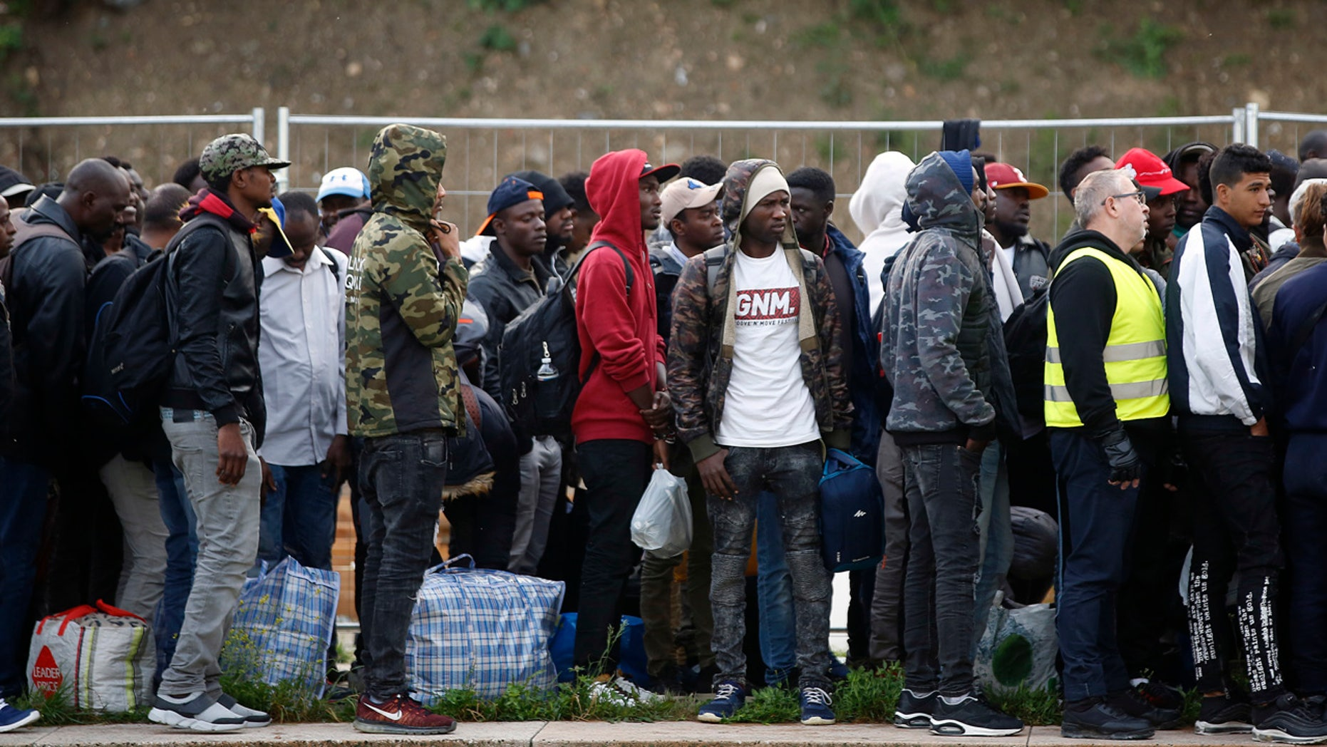 May 30: Migrants line up in a makeshift camp during its evacuation, in Paris. Authorities moved in on the so-called Millennaire tent camp on the city's edge alongside a canal used by joggers and cyclists.