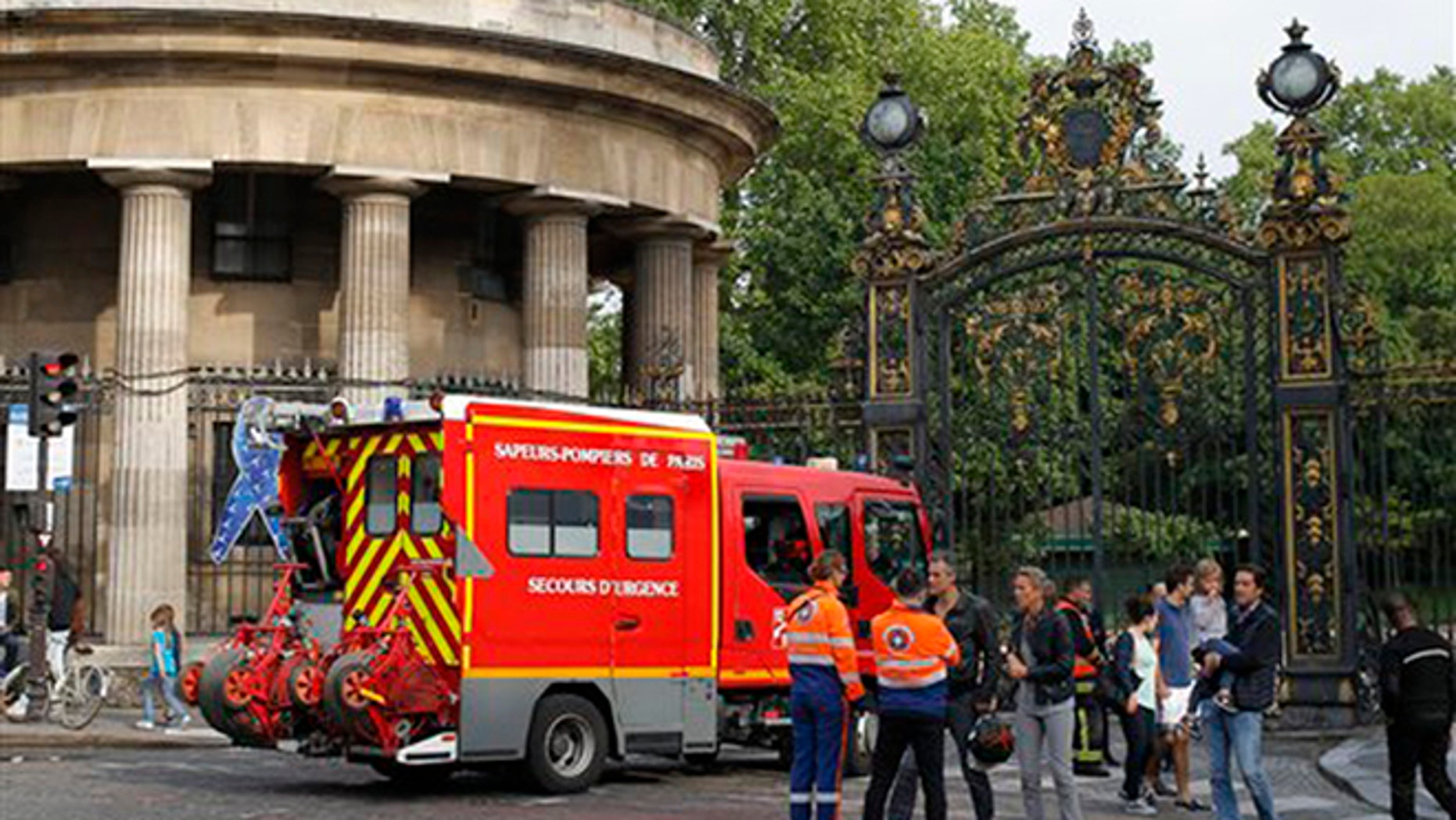 A fire truck is parked at the entrance to Monceau parc in the center of Paris, France, Saturday, May 28, 2016, after a lightning bolt crashed down onto a Paris park, striking 11 people at a child's birthday party. (AP Photo/Francois Mori)