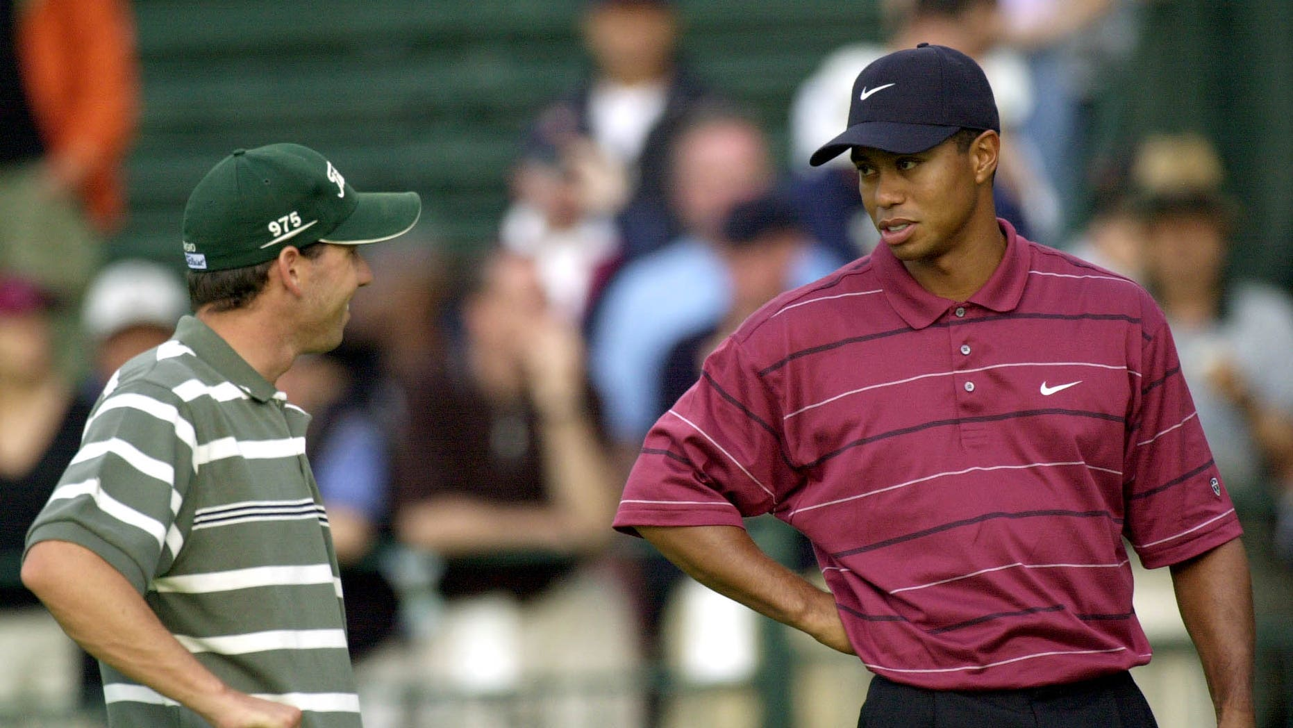 """FILE - In this June 16, 2002 file photo, Sergio Garcia, left, and Tiger Woods talk on the 11th hole while waiting for play to resume after a rain delay during the final round of the U.S. Open Golf Championship in Farmingdale, N.Y.  Garcia was at a European Tour awards dinner Tuesday night, May 21, 2013 when he was jokingly asked if he would have Woods over for dinner during the U.S. Open. The Spaniard replied, """"We'll have him round every night. We will serve fried chicken."""" Woods took to Twitter on Wednesday, May 22, 2013 and said the comment wasn't silly, rather it was wrong and hurtful. (AP Photo/Dave Martin, File)"""