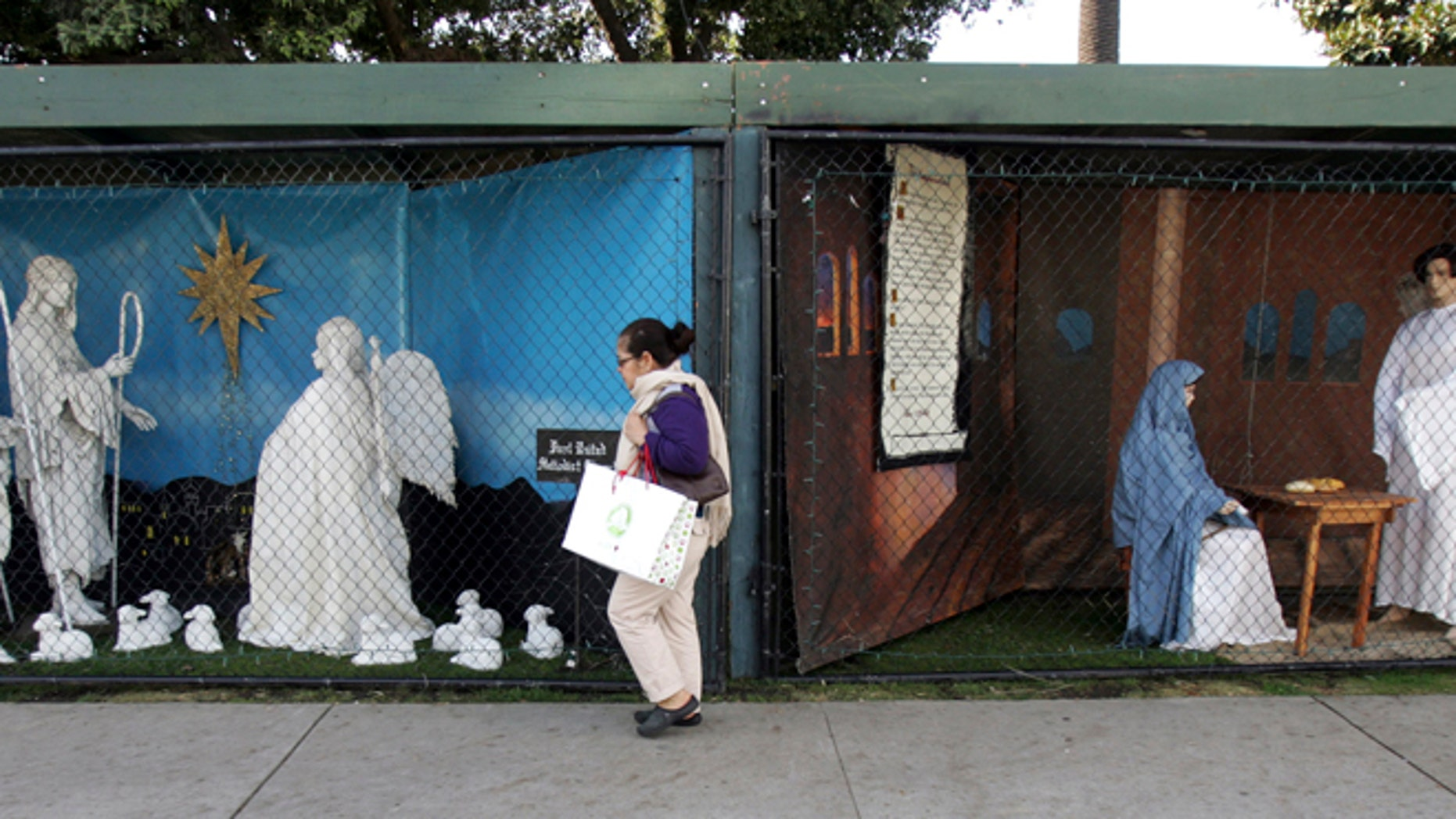 Dec. 13, 2011: A woman walks past a two of the traditional displays showing the Nativity scene along Ocean Avenue at Palisades Park in Santa Monica, Calif.
