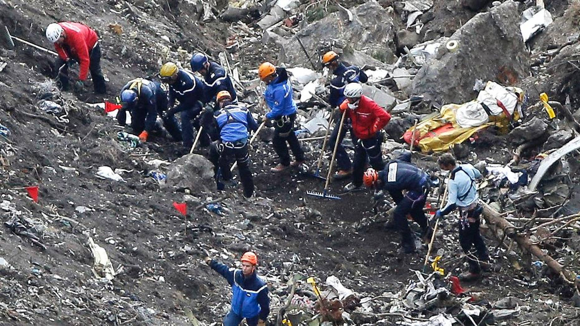 FILE - In this Thursday March 26, 2015 file photo, rescue workers inspect the debris from the Germanwings jet at the crash site near Seyne-les-Alpes, France. The somber mission to recover the remains of 150 people killed instantly when the Germanwings flight crashed full speed into the Col de Mariaud is not a quiet one and crucial physical evidence for the crash investigation can be gathered only when the mountains cooperate. (AP Photo/Laurent Cipriani, File)