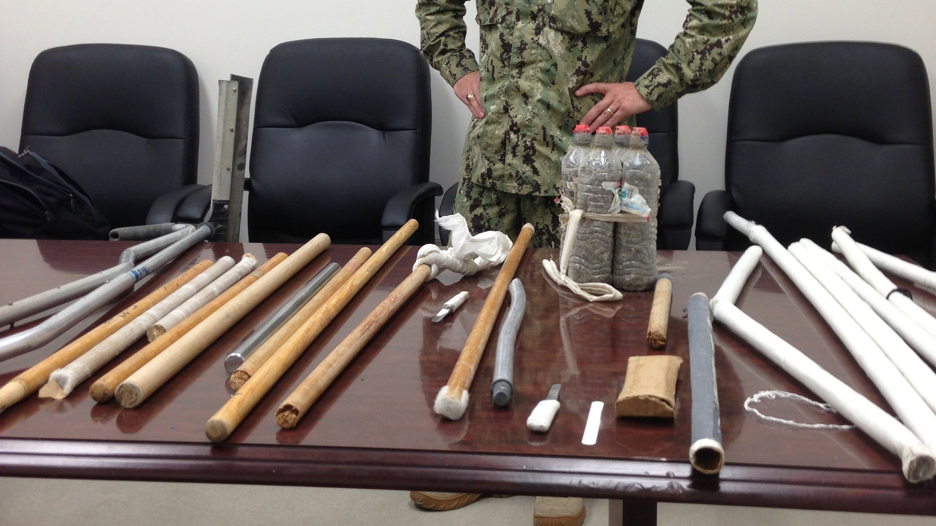 In this image reviewed by the U.S. Military, Navy Capt. Robert Durand stands next to some of the makeshift weapons, including broomsticks and batons made of plastic and steel, that were confiscated from prisoners at the Guantanamo Bay prison following a Saturday clash between prisoners and guards, on display for the press at the U.S. Naval Base Guantanamo Bay in Cuba, Tuesday, April 16, 2013. Soldiers with riot helmets and shields swept into recreation yards and met with resistance from several dozen prisoners, the leadership of the detention center said. The guard force raided Camp 6 because the prisoners had for several weeks covered up 147 of the 160 security cameras, making it impossible to monitor them amid a weeks long hunger strike.  The hunger strike goes on, with 45 prisoners refusing meals and 13 being force fed, officials said. (AP Photo/Ben Fox)