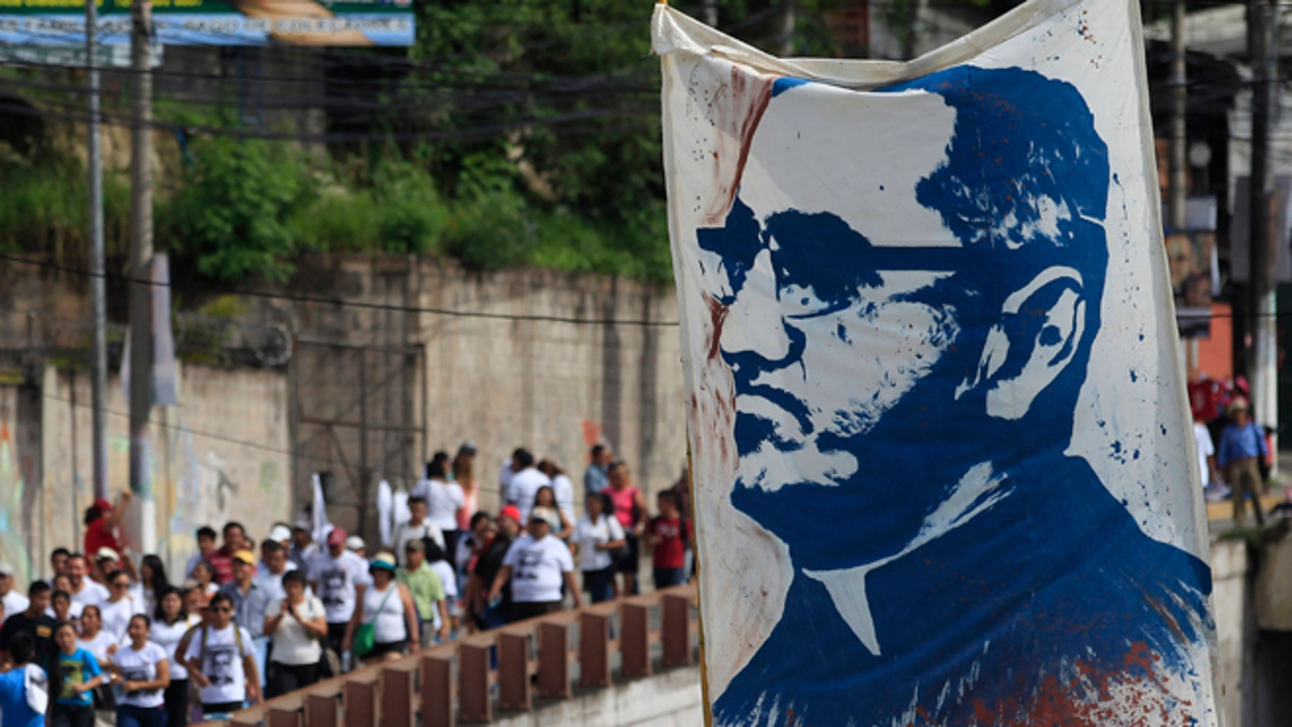 Pilgrims carry a portrait of Archbishop Oscar Romero in San Salvador, Saturday, May 23, 2015.