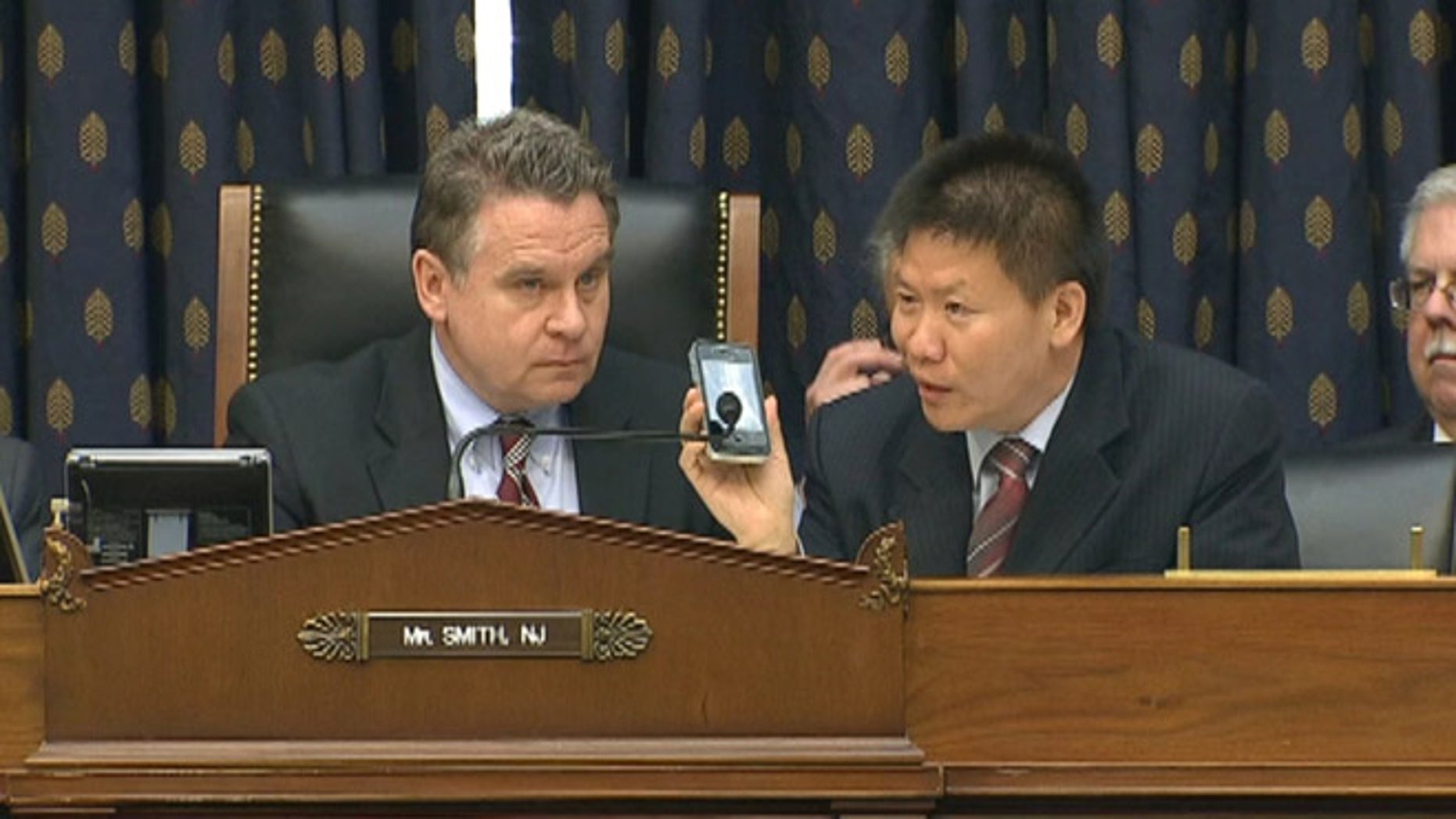 May 3, 2012: Rep. Chris Smith, left, and ChinaAid President Bob Fu, right, listen as Chinese activist Chen Guangcheng addresses a Capitol Hill committee over the phone.