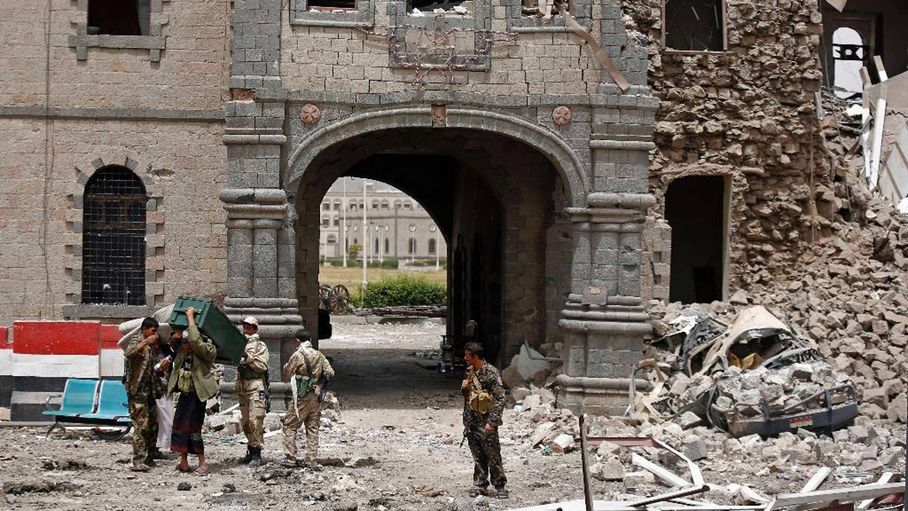 Shiite rebels known as Houthis wearing army uniforms stand guard in front of Yemen's Defense Ministry building after it was damaged by Saudi-led airstrikes in Sanaa, Yemen, Wednesday, June 10, 2015. A series of airstrikes by the Saudi-led military coalition on Tuesday struck the building, which is under the control of Shiite rebels who last year seized the capital, Sanaa, officials said. (AP Photo/Hani Mohammed)