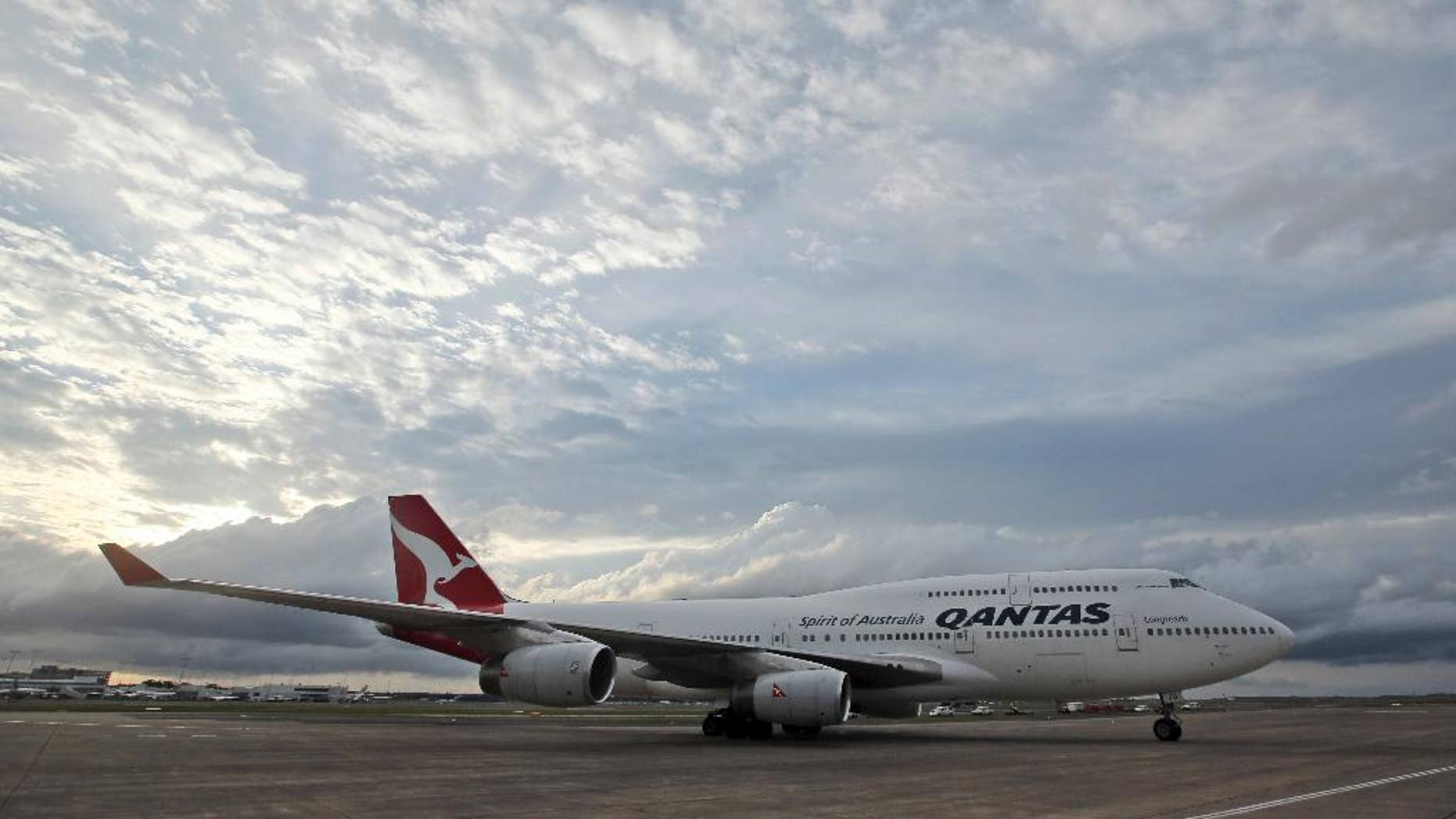 FILE - In this Tuesday, Sept. 13, 2016 file photo, a Qantas jet taxis on the runway at Sydney Airport in Sydney, Australia. Around 100 passengers on board a Qantas regional jet in Australia were evacuated via the plane's emergency slides upon landing on Friday, Sept. 23 after the crew noticed fumes inside the cabin, officials said. (AP Photo/Rob Griffith, File)