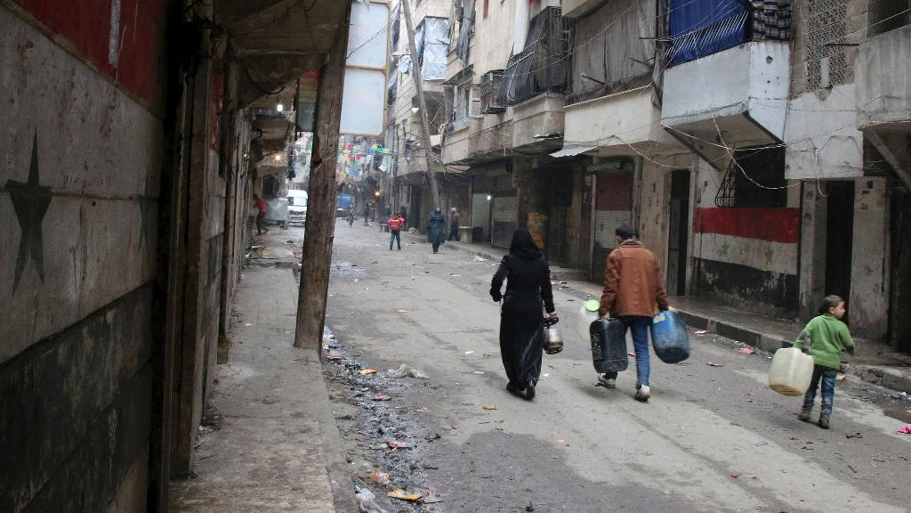 FILE -- In this February 11, 2016, file photo, civilians walk with containers for fuel and water in Aleppo, Syria. Dozens of State Department employees have endorsed an internal document that advocates U.S. military action to pressure Syria's government into accepting a ceasefire and engaging in peace talks, officials said Thursday. The position is at odds with U.S. policy. (Alexander Kots/Komsomolskaya Pravda via AP, File)