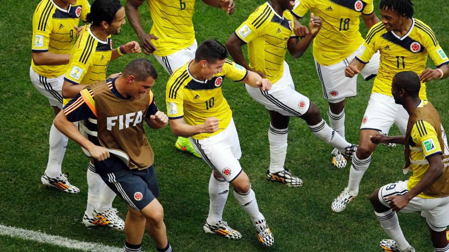 FILE - In this June 19, 2014, file photo, Colombia's James Rodriguez, center, dances with teammates in celebration after scoring during the group C World Cup soccer match between Colombia and Ivory Coast at the Estadio Nacional in Brasilia, Brazil. The euphoria in soccer-mad Colombia is deafening, and wonderfully contagious, ahead of Friday's do-or-die World Cup match against host Brazil. Not since Colombia drubbed Argentina 5-0 in a 1993 World Cup qualifier has the South American nation of 48 million been so enthralled by the beautiful game. (AP Photo/Themba Hadebe, File)