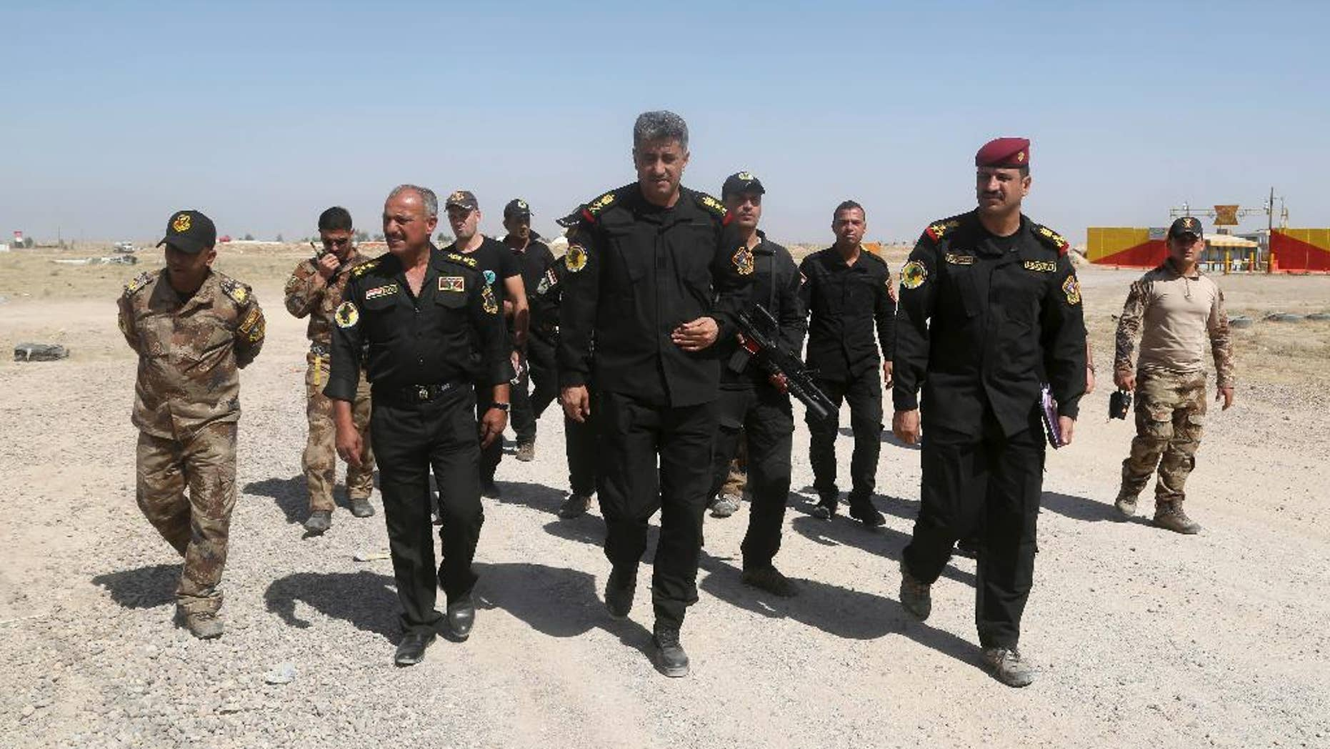 Commander of the Fallujah operation, Lt. General Abdul-Wahab al-Saadi, center, inspects his forces ahead of an operation to re-take the Islamic State-held City of Fallujah, outside Fallujah, Iraq, Sunday, May 29, 2016. Teaming up with paramilitary troops and backed by aerial support from the U.S.-led coalition, Iraqi government launched a large-scale offensive to dislodge IS militants from the city of Fallujah, one of the last major IS strongholds in Iraq located about 40 miles (65 kilometers) west of Baghdad. (AP Photo/Khalid Mohammed)