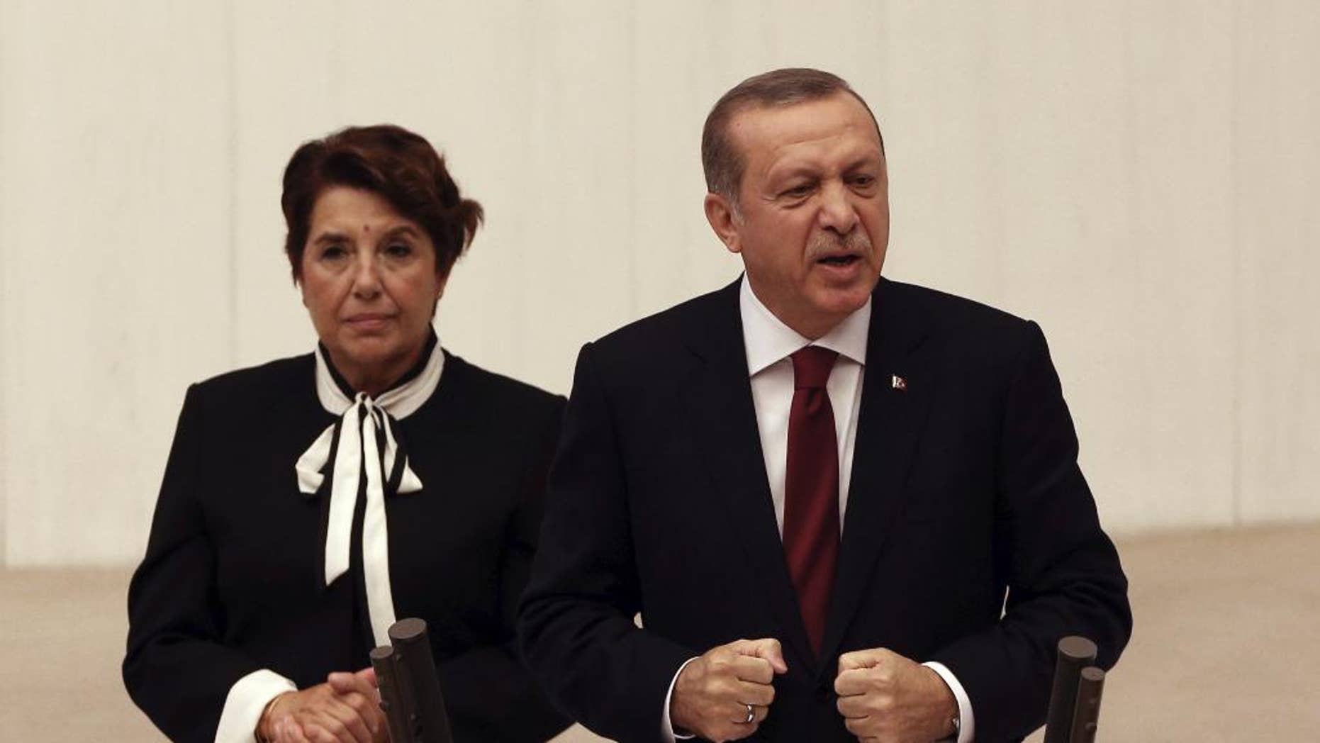 Turkey's President Recep Tayyip Erdogan addresses the parliament in Ankara, Turkey, Saturday, Oct. 1, 2016. Erdogan hinted on Thursday that the three-month state of emergency declared following the failed July 15 coup could be extended to over a year. Aysenur Bahcekapili, a lawmaker from the ruling Justice and Development Party, stands during his speech. (AP Photo/Burhan Ozbilici)