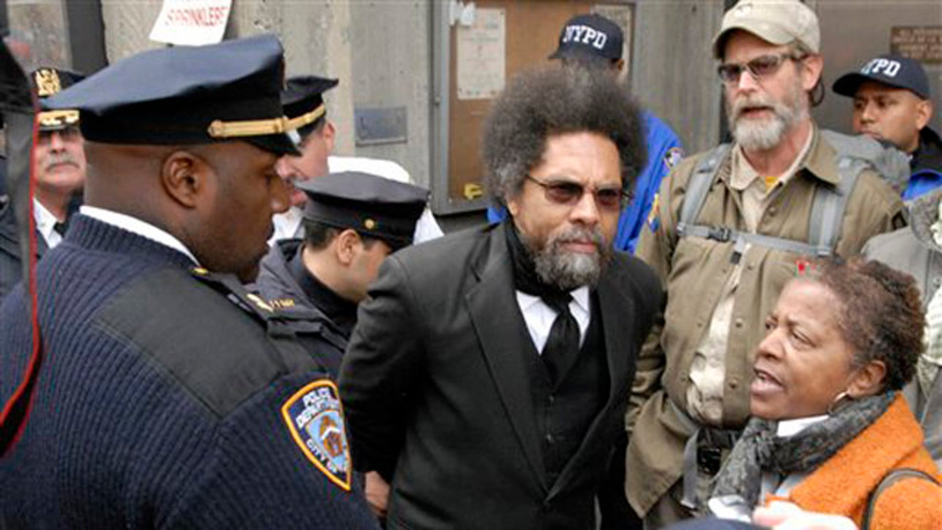 """Oct. 21, 2011: Political activist, Dr. Cornel West, center, is taken into custody by New York City police officers at a """"Stop and Frisk"""" policy protest in Manhattan's Harlem neighborhood in New York."""