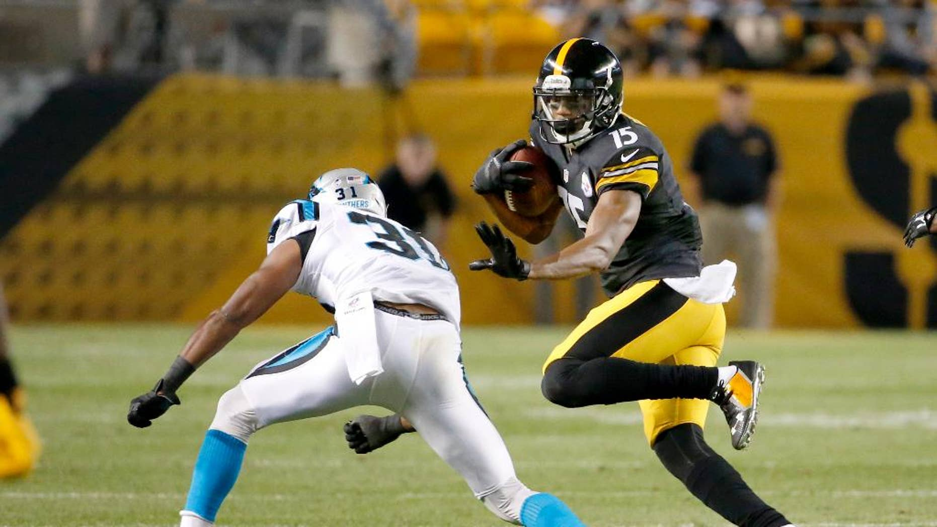 Pittsburgh Steelers wide receiver Justin Brown (15) tries to evade Carolina Panthers defensive back James Dockery (31) in the second quarter of a NFL preseason football game on Thursday, Aug. 28, 2014 in Pittsburgh. (AP Photo/Gene Puskar)