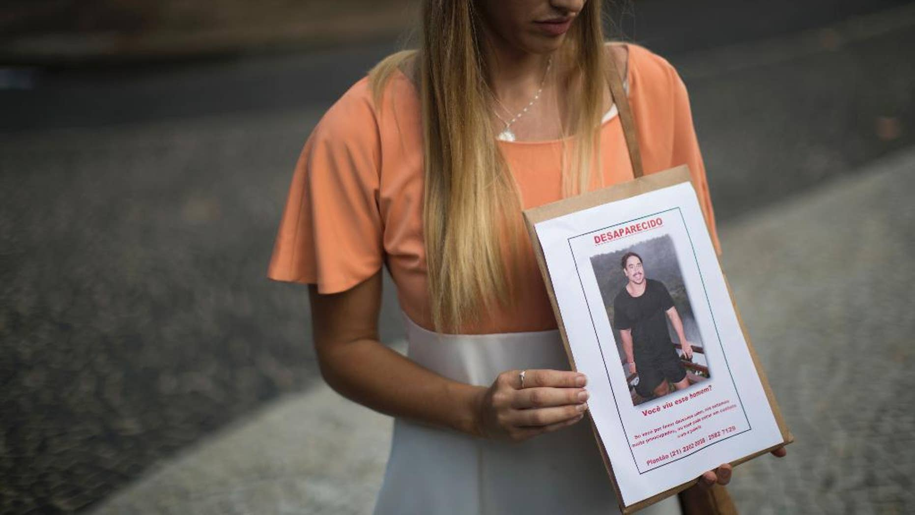 FILE - In this June 3, 2016 file photo, Bonnie Cuthbert, of Australia, shows a photo of her missing boyfriend Rye Hunt, 25, during a press conference in Rio de Janeiro, Brazil. Hunt, an electrician who worked at a mine in western Australian, was in Rio as part of a world trip with a friend where he was last seen on May 21. On Saturday, June 11, police confirmed that the body that washed up on a beach near Rio de Janeiro three days prior is Hunt, adding that investigators have not been able to establish the cause of death. (AP Photo/Felipe Dana, File)