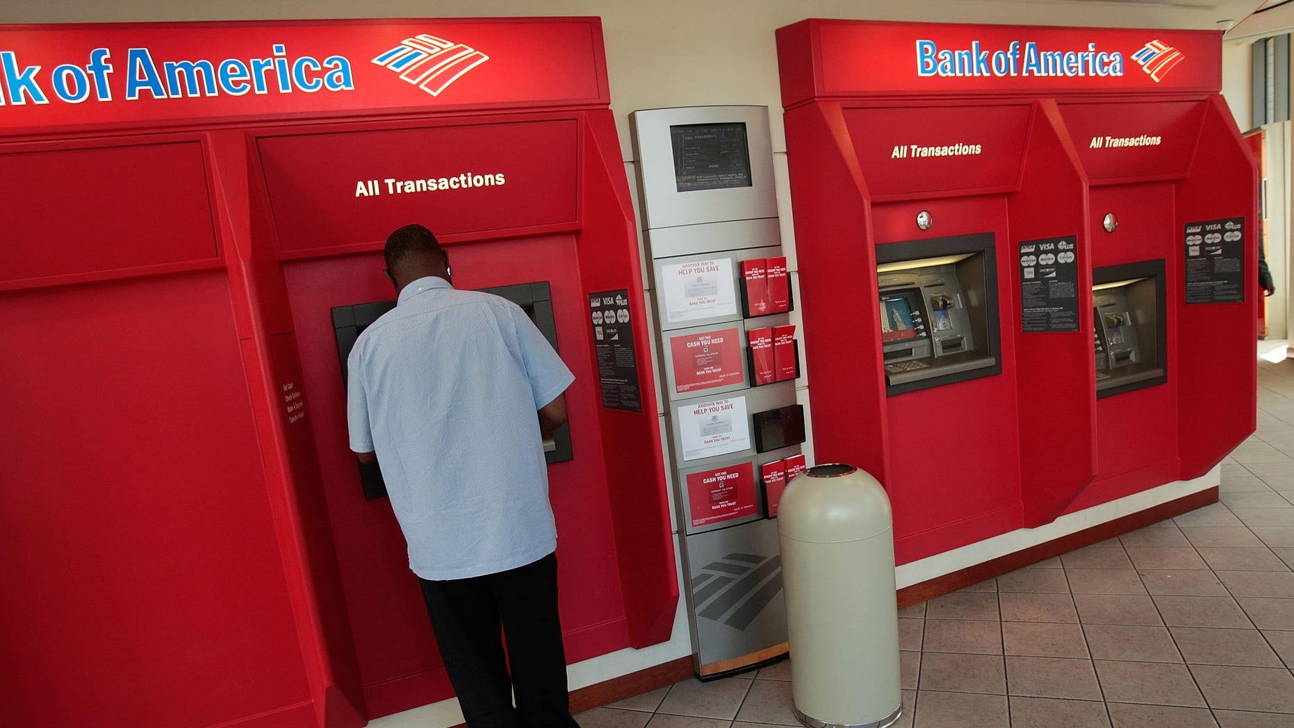 NEW YORK - JULY 21:  A man operates an automated teller machine at a  Bank of America branch bank in midtown Manhattan July 21, 2008 in New York City. Bank of America Corp. reported falling profits of 41-percent to $3.41 billion in their second quarter earnings but nonetheless beating analysts' 54-percent estimates, sending their stock price higher to $30.24 a share in morning trading.  (Photo by Chris Hondros/Getty Images)