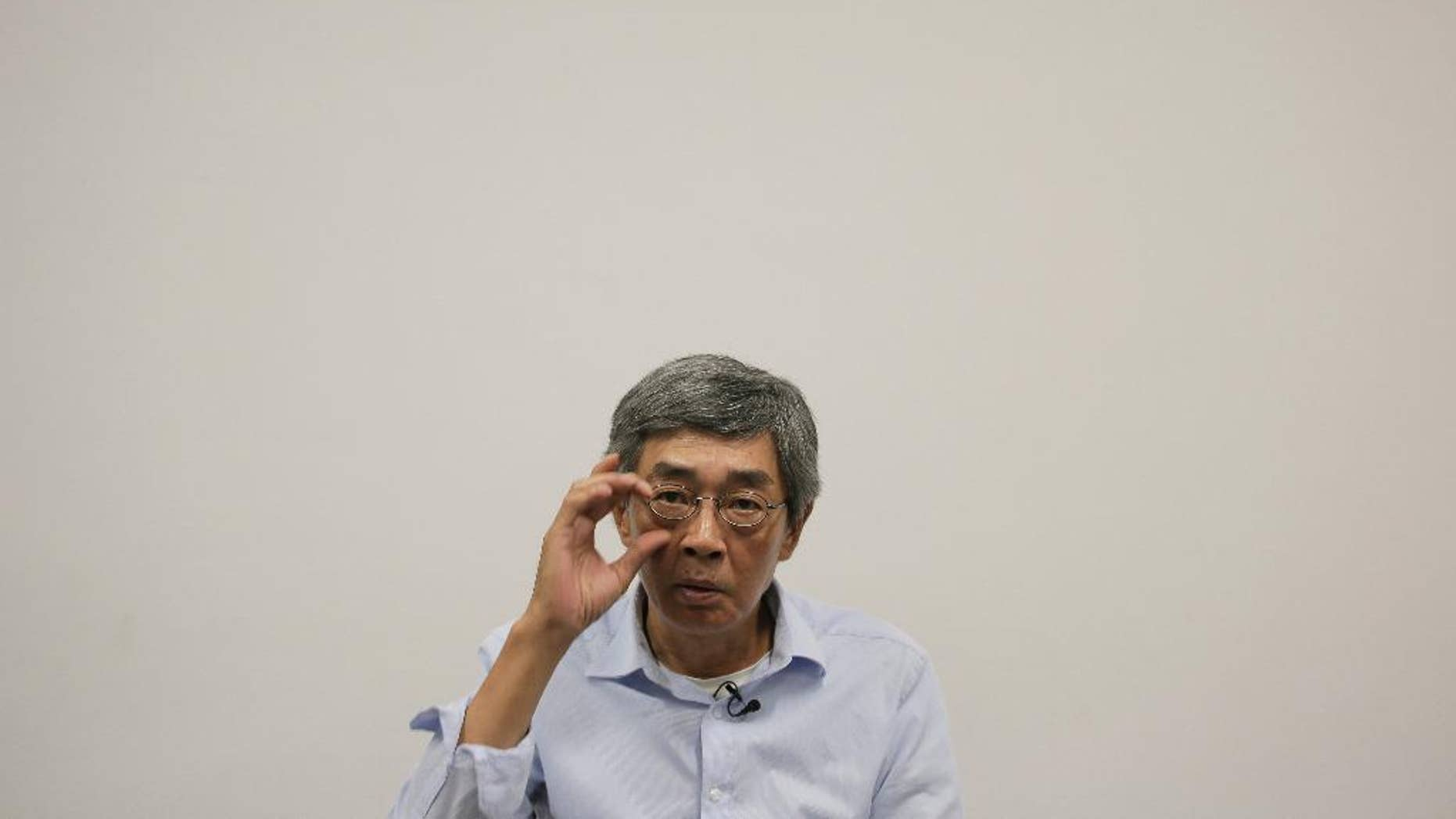 In this Sunday, June 19, 2016 photo, Hong Kong bookseller Lam Wing-kee reacts during an interview in Hong Kong. Hong Kong officials say there's little chance Lam, who is wanted in mainland China, would be sent back after mainland authorities threatened him with tougher punishment if he didn't return. (AP Photo/Vincent Yu)