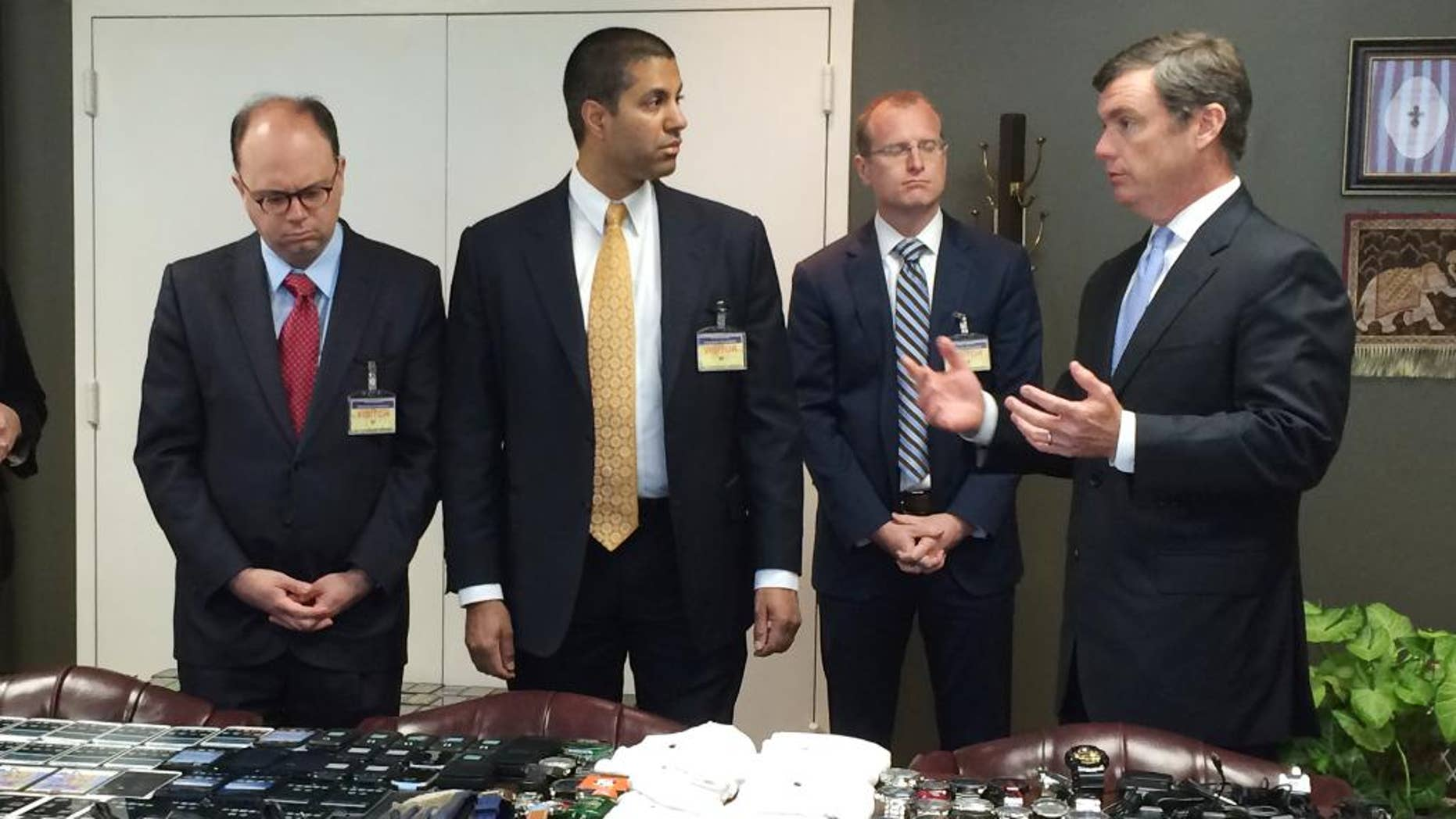 In this photo made available by the South Carolina Department of Corrections on Wednesday, April 6, 2016, their director, Bryan Stirling, right, showing hundreds of cellphones that were seized in a single raid from the Lee Correctional Institution, S.C. Stirling speaks to FCC official Matthew Berry, left, FCC Commissioner Ajit Pai and FCC official Brendan Carr. Stirling wants federal officials to allow the state to block cell signals so contraband phones become useless to inmates. (Stephanie Givens, South Carolina Department of Corrections via AP)